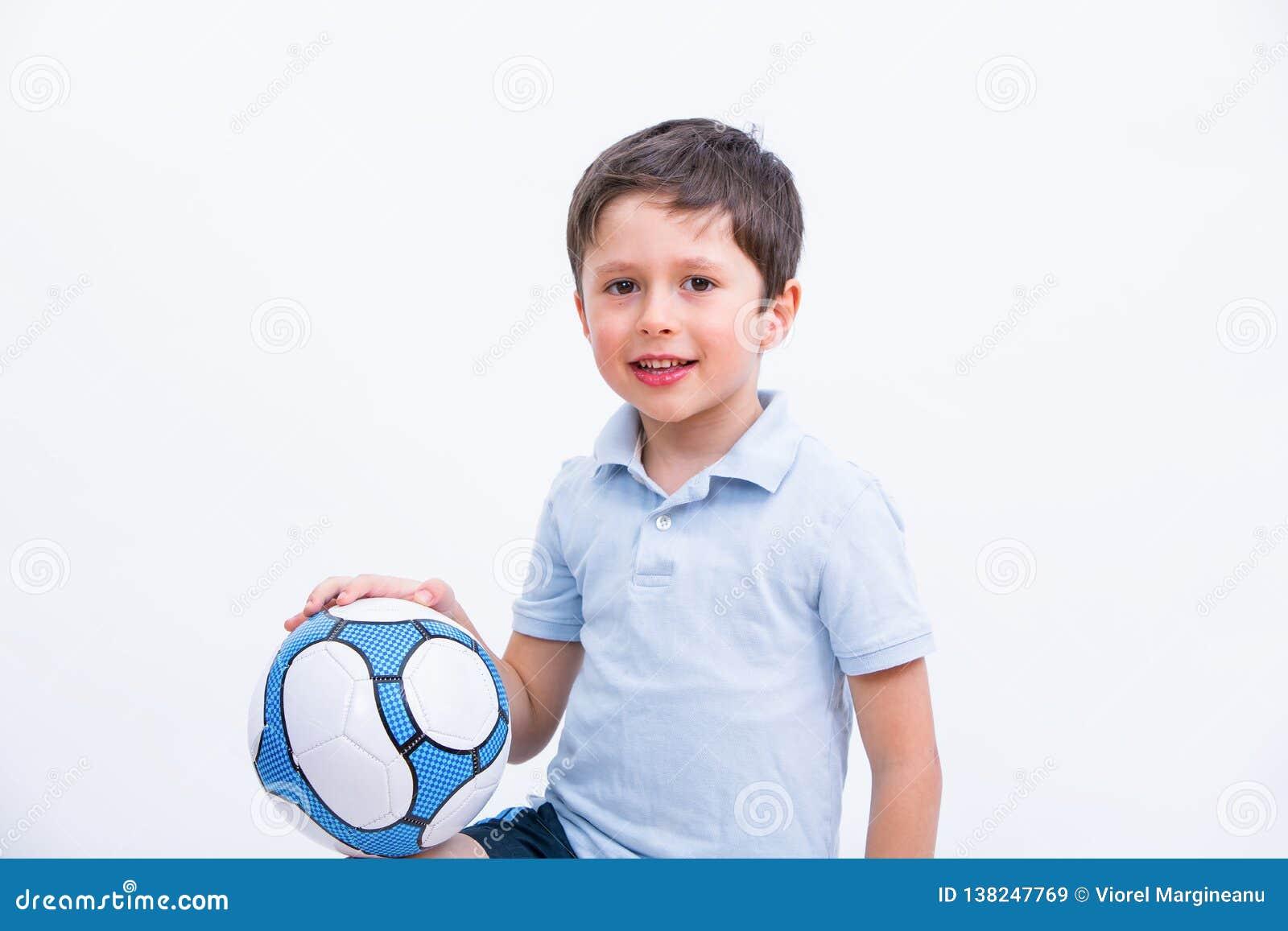 Szczęśliwa chłopiec bawić się futbol Śliczny dziecko, młody męski nastoletni bramkarz cieszy się sport grę Mała futbolisty mienia