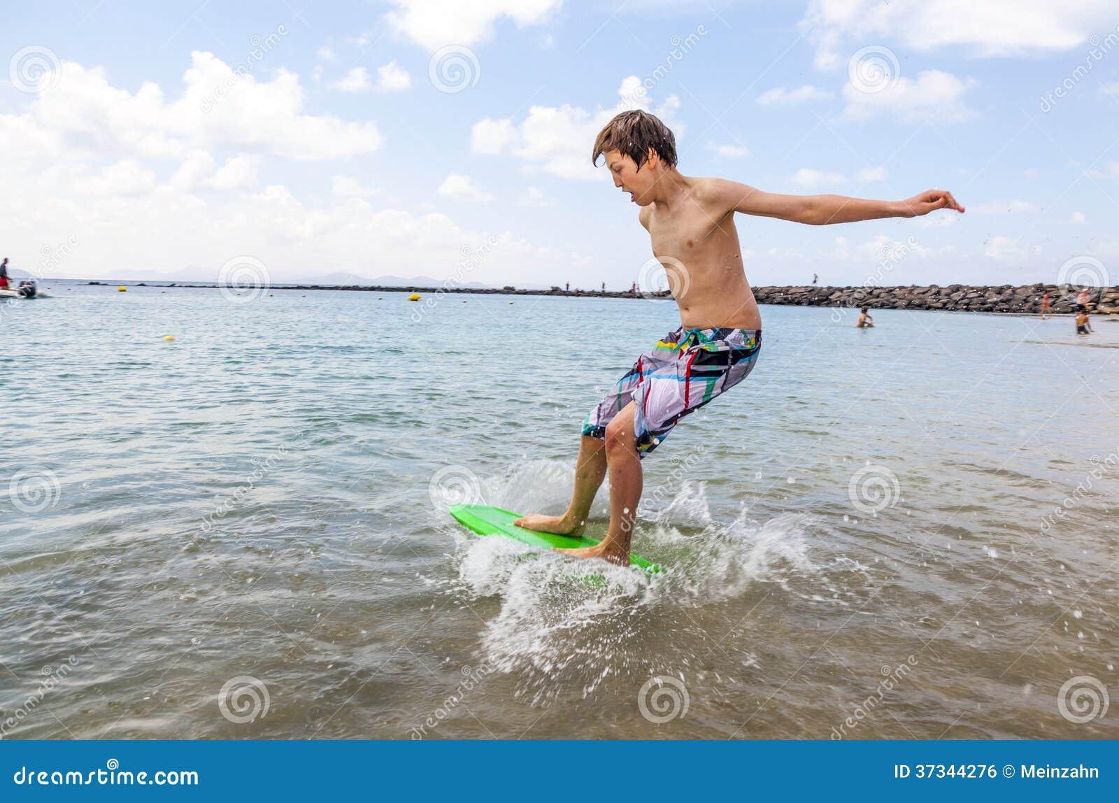 Szczęśliwa chłopiec cieszy się surfing w fala