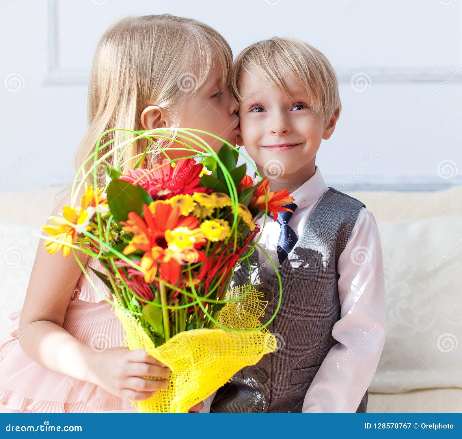 Szczęśliwa chłopiec daje bukietowi dla ślicznej dziewczyny