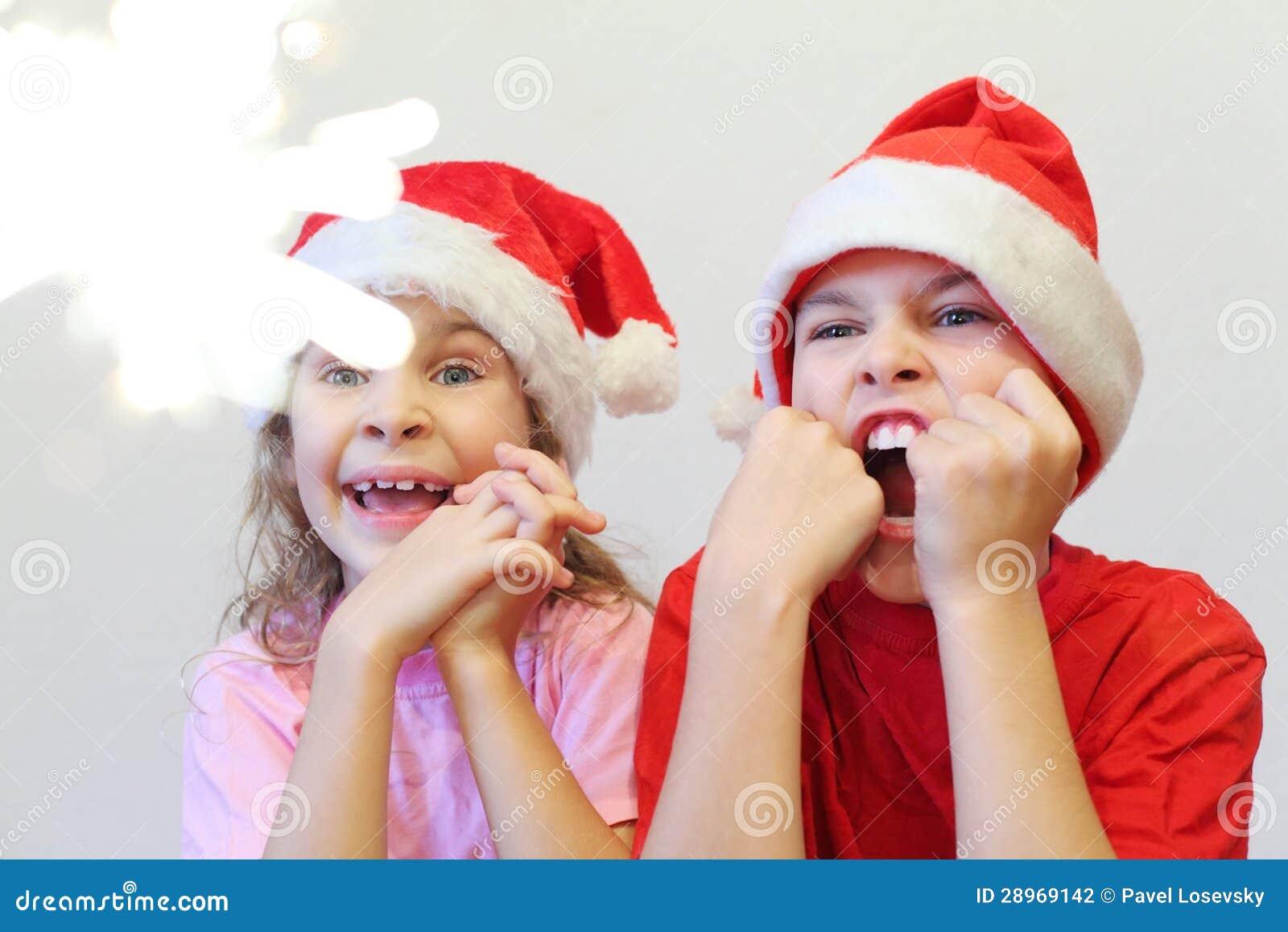Szczęśliwa chłopiec i dziewczyna w Bożenarodzeniowych czerwonych nakrętkach