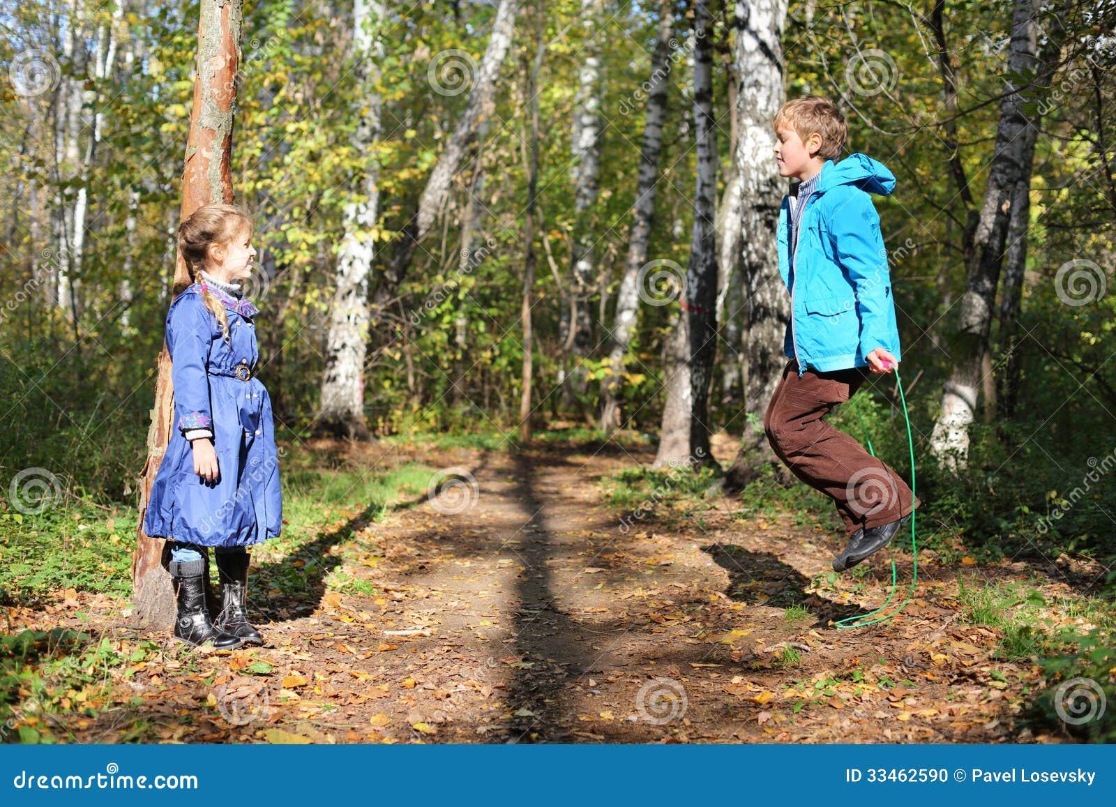 Szczęśliwa chłopiec skacze z omijać arkany i dziewczyny spojrzenia przy on