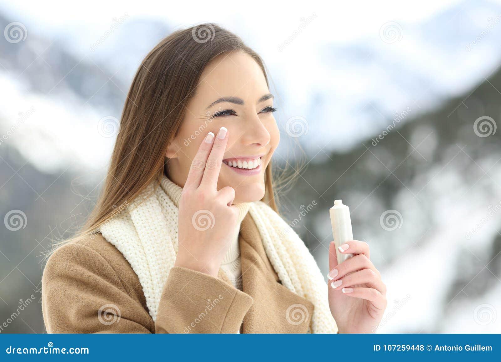 Szczęśliwa dama stosuje twarzową moisturizer śmietankę w zimie