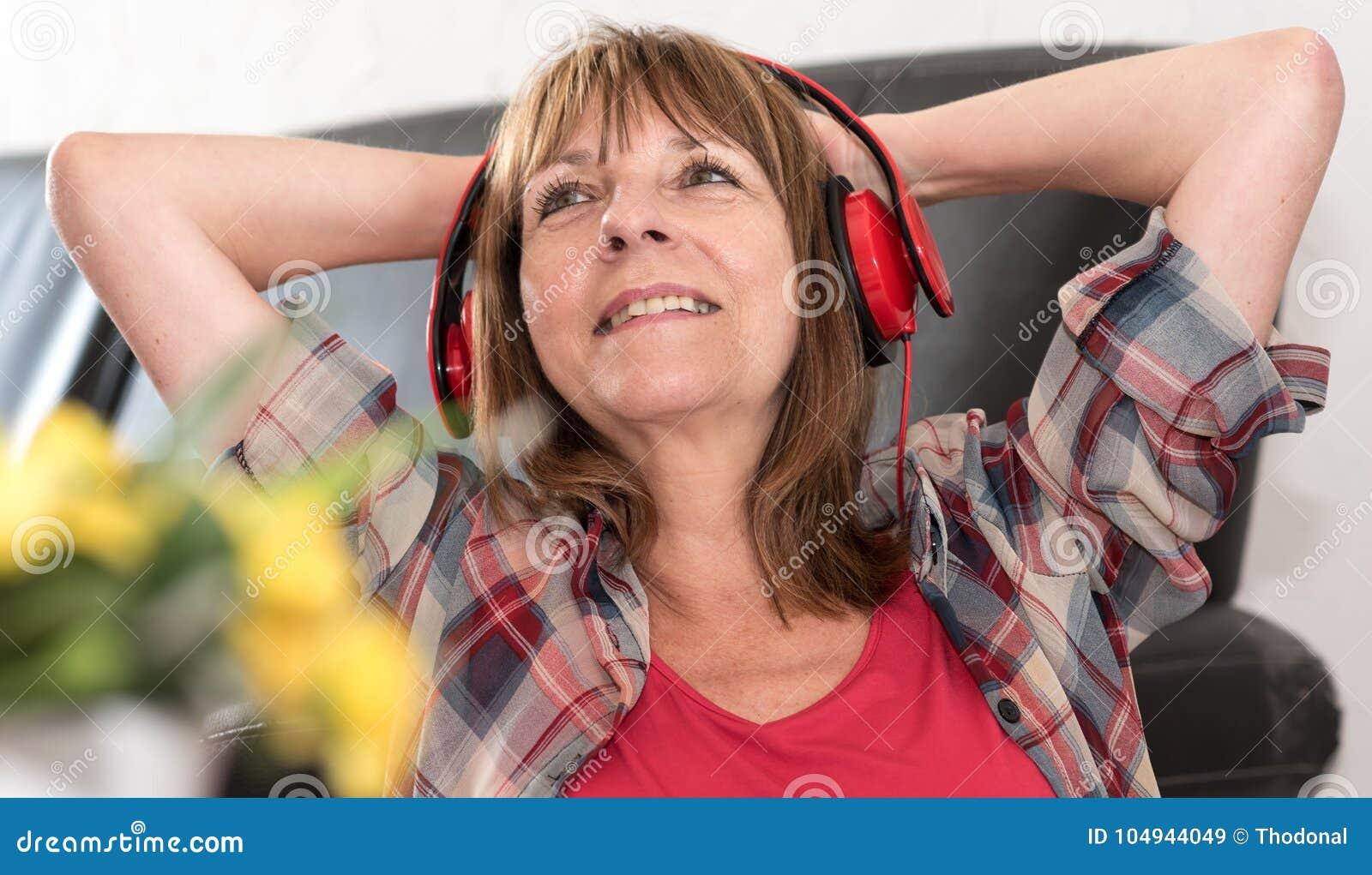 Szczęśliwa dojrzała kobieta słucha muzyka