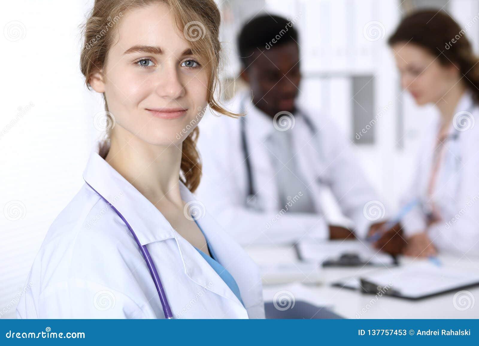 Szczęśliwa doktorska kobieta z medycznym personelem przy szpitalem Wielo- etniczni ludzie grup