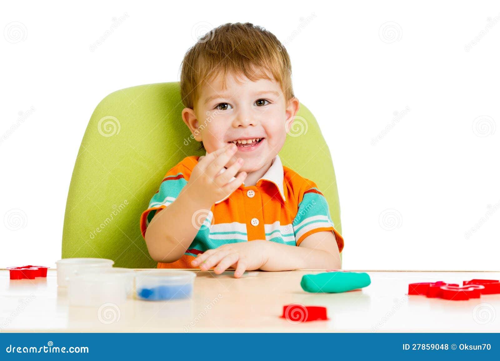 Szczęśliwa dziecka chłopiec bawić się z kolorową gliną