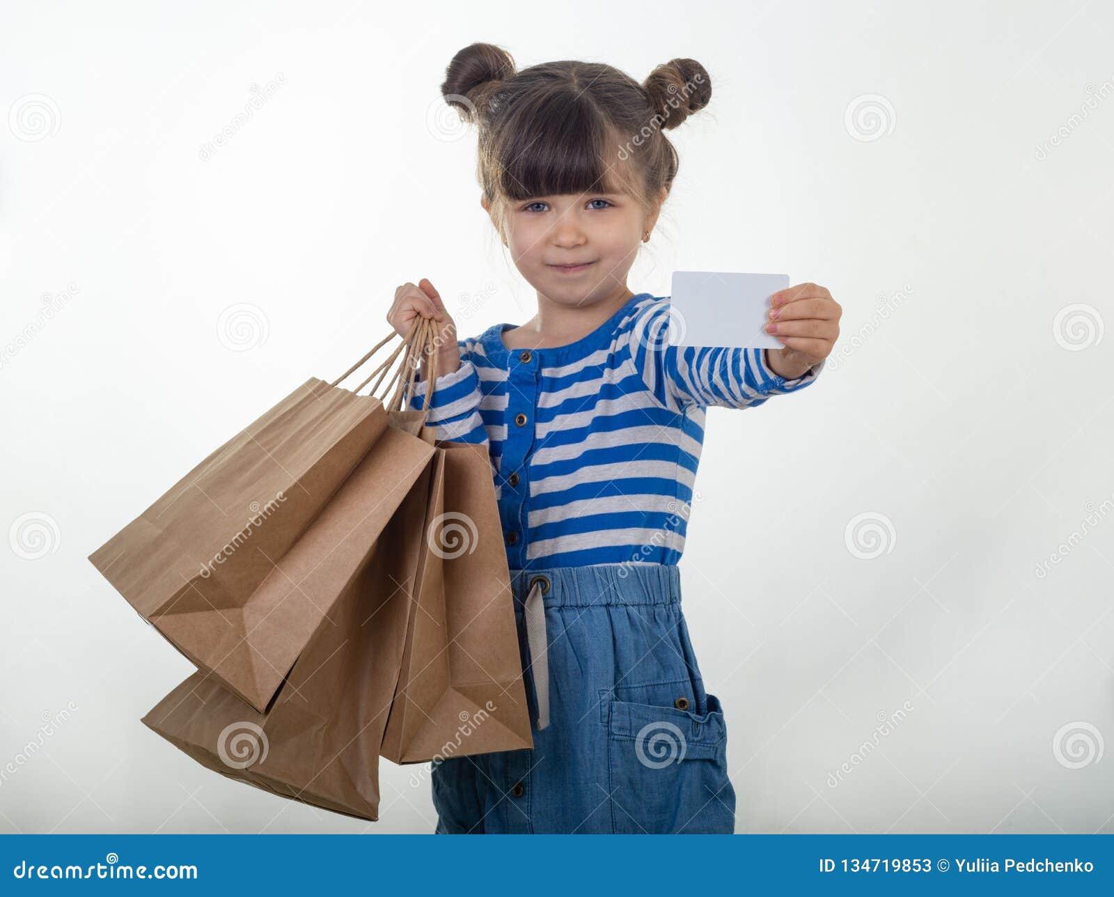 Szczęśliwa dziecka mienia rabata bielu karta i torby na zakupy w jej rękach Dzieciak z kartą kredytową