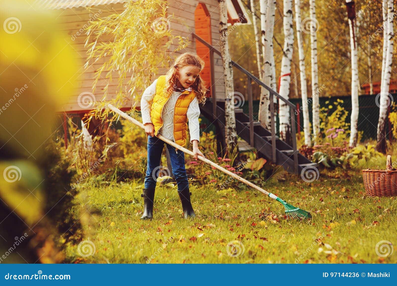 Szczęśliwa dziecko dziewczyna bawić się małej ogrodniczki w jesieni i podnosi opuszcza w kosz Sezonowa ogrodowa praca