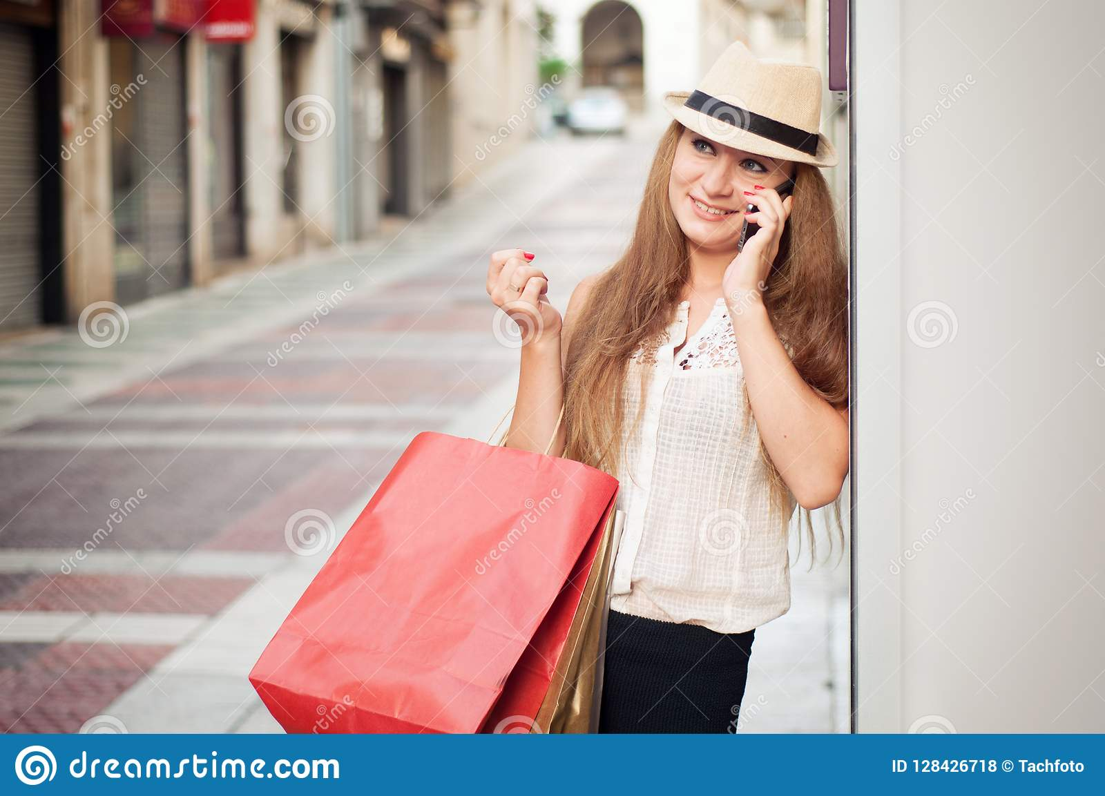 Szczęśliwa dziewczyna chodzi przez ulicy po robić zakupy Ona mienie