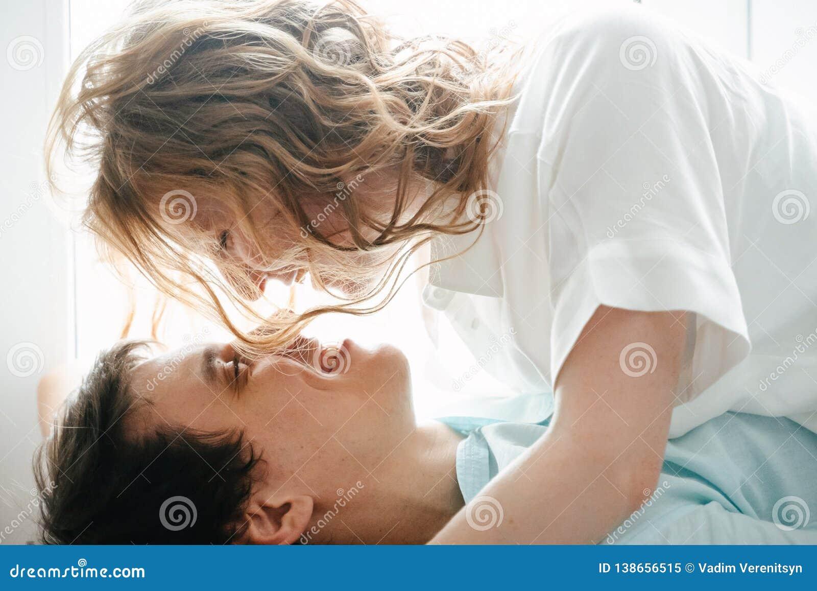 Szczęśliwa dziewczyna i mężczyzna ściska blisko okno w domu