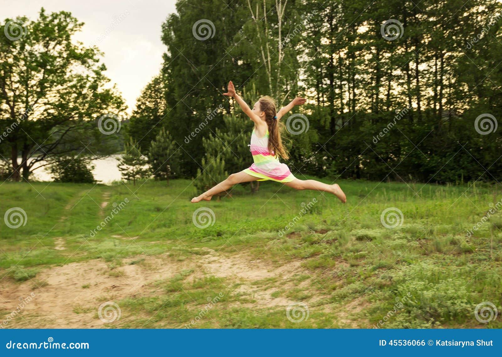 Szczęśliwa dziewczyna skacze niebo w żółtej łące przy zmierzchem