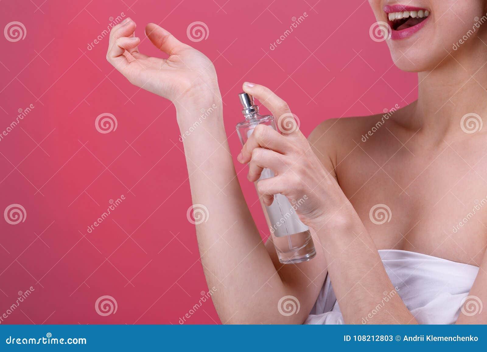 Szczęśliwa dziewczyna stosuje pachnidło nadgarstku teren i uśmiecha się ślicznego Na różowym tle Zakończenie