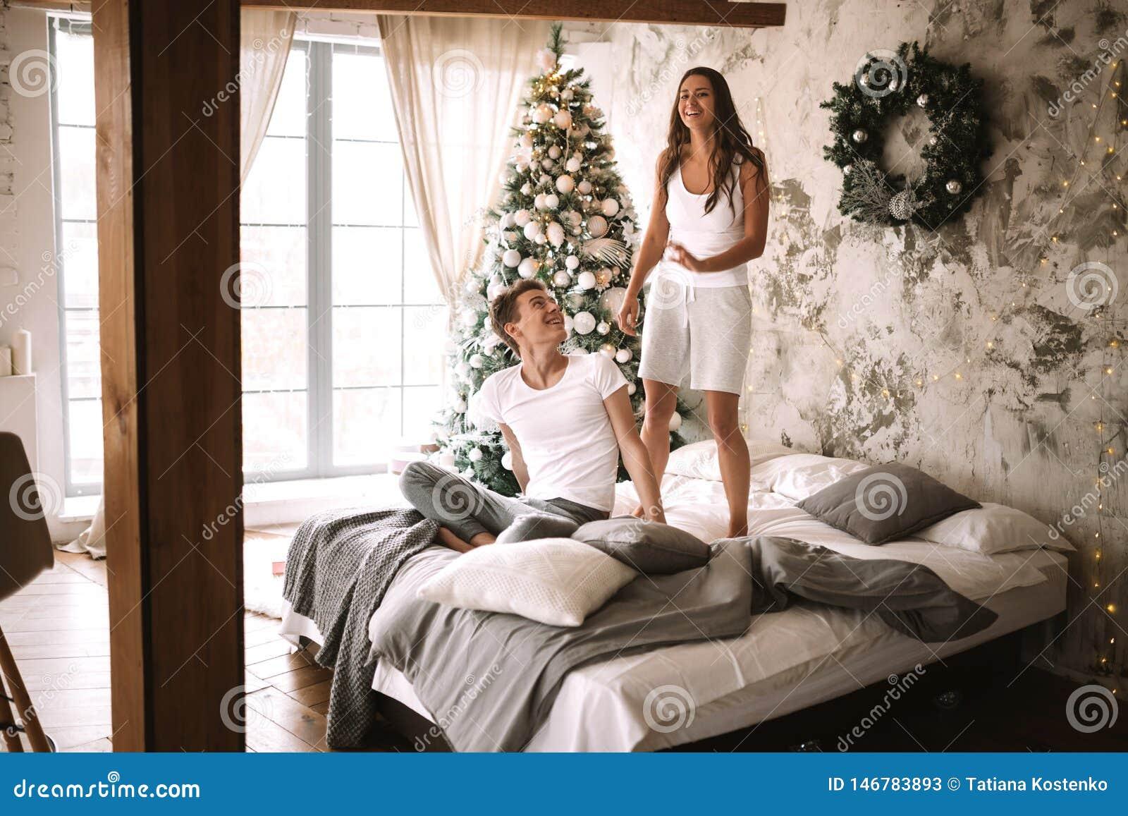 Szczęśliwa dziewczyna ubierająca w białych skrótach i koszulkach skacze na łóżku obok faceta siedzi tam w wygodnym dekorującym