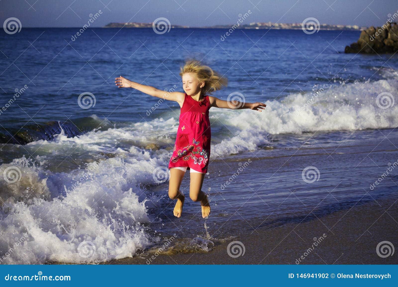 Szczęśliwa dziewczyna w barwionym smokingowym doskakiwaniu na falach na plaży