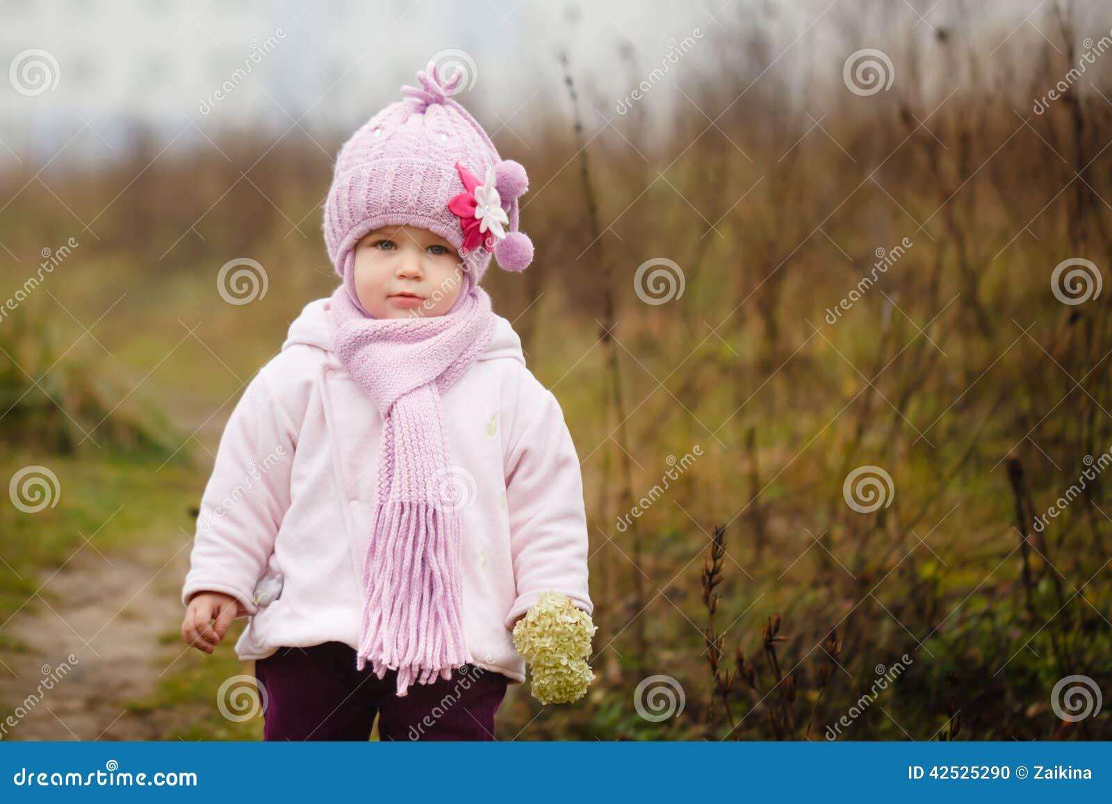 Szczęśliwa dziewczynka w różowym szaliku i kapeluszu śmia się