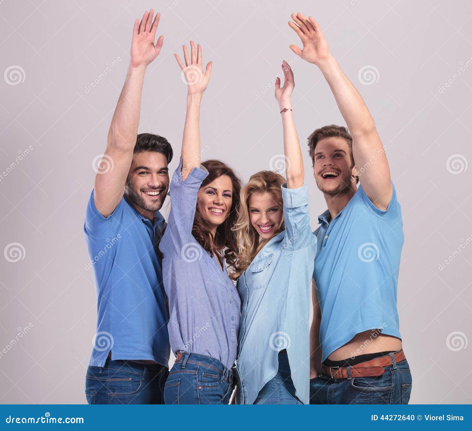 Szczęśliwa grupa młodzi ludzie świętuje sukces z ręki podwyżką