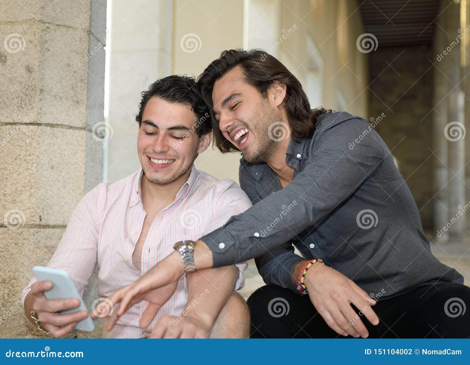 Szczęśliwa homoseksualna para ono uśmiecha się z ich telefonem komórkowym