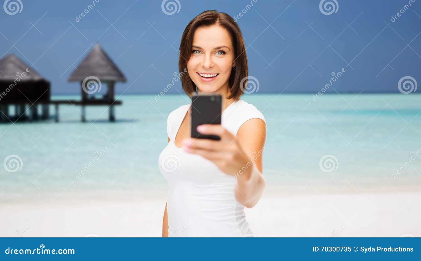 Szczęśliwa kobieta bierze obrazek smartphone na plaży
