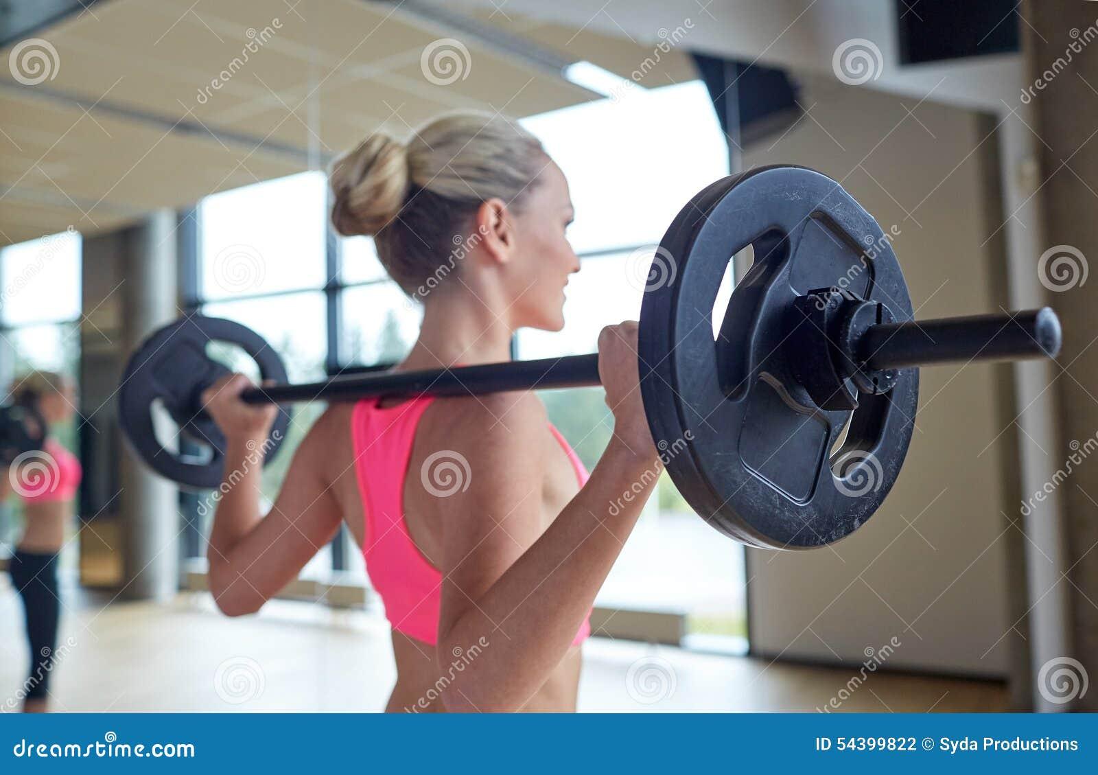 Szczęśliwa kobieta napina mięśnie z barbell w gym