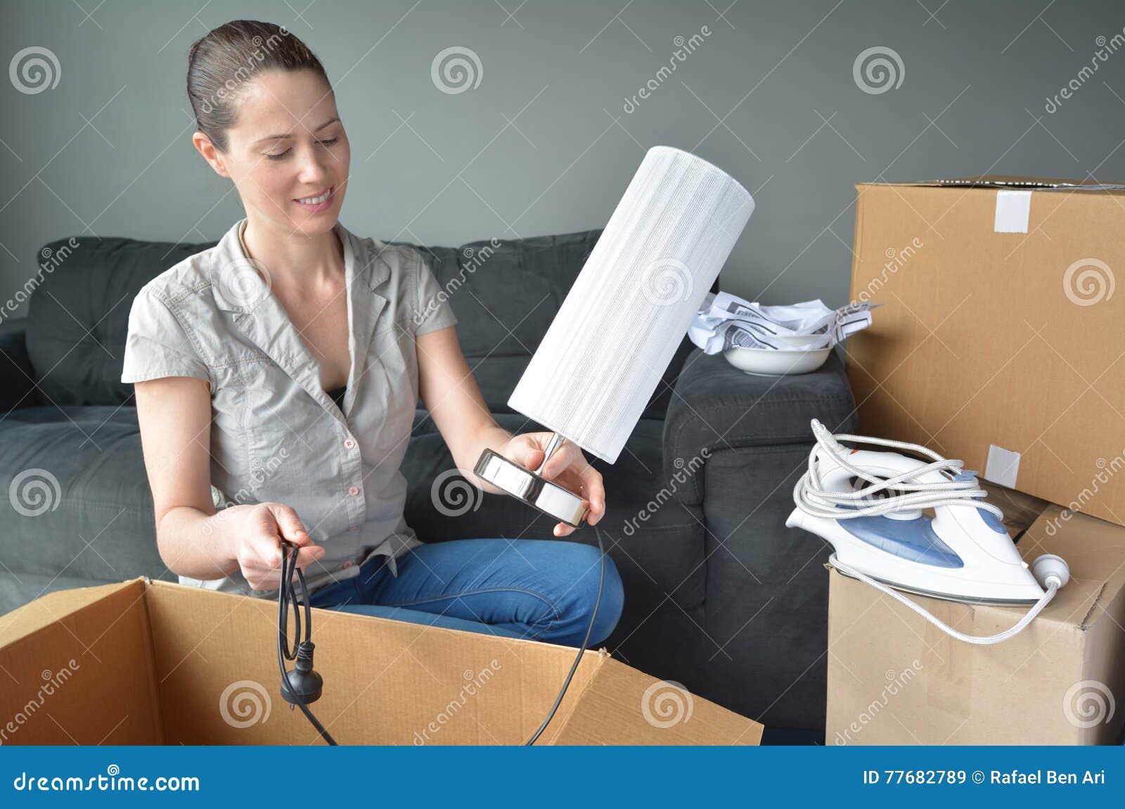 Szczęśliwa kobieta odpakowywa pudełka podczas ruchu w nowego dom
