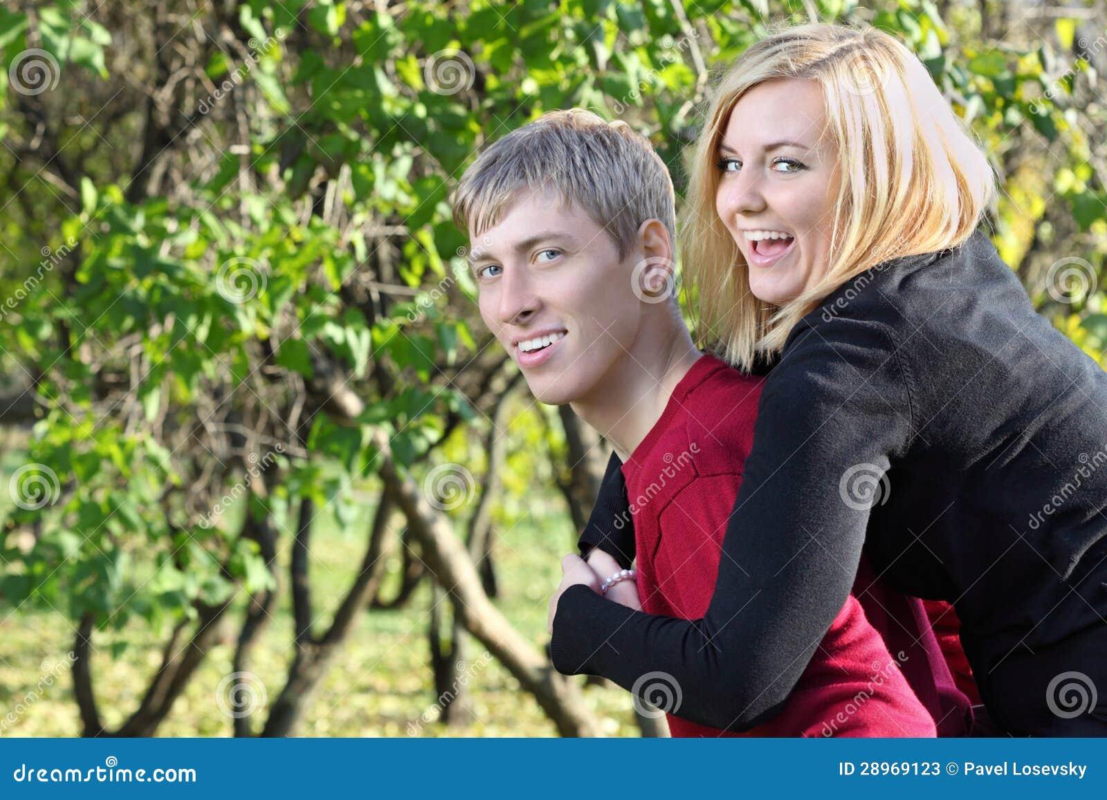 Szczęśliwa kobieta siedzi na plecy mężczyzna i śmia się w parku