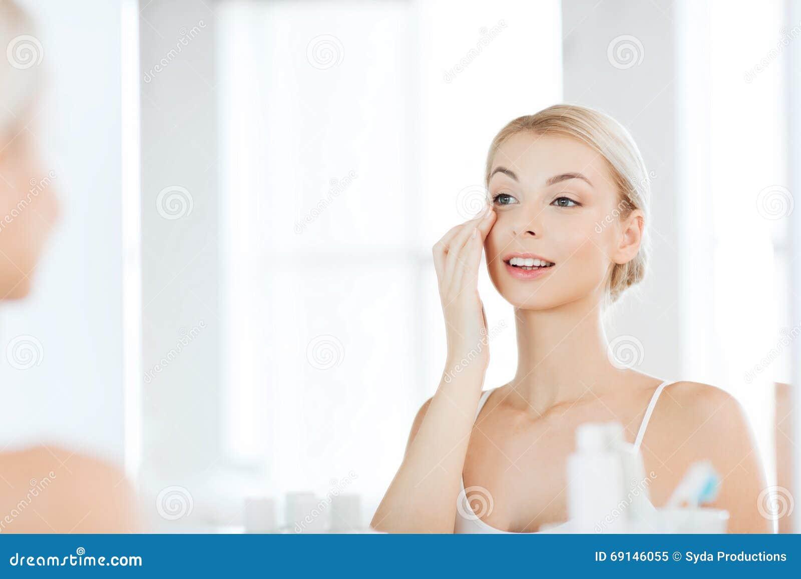 Szczęśliwa kobieta stosuje śmietankę twarz przy łazienką