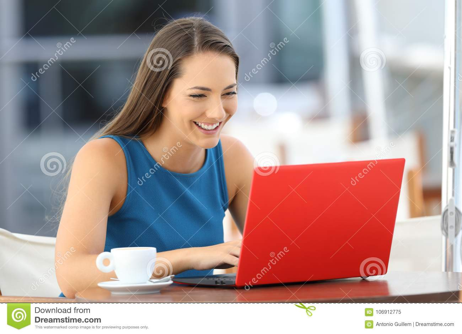 Szczęśliwa kobieta używa czerwonego laptop w prętowym tarasie