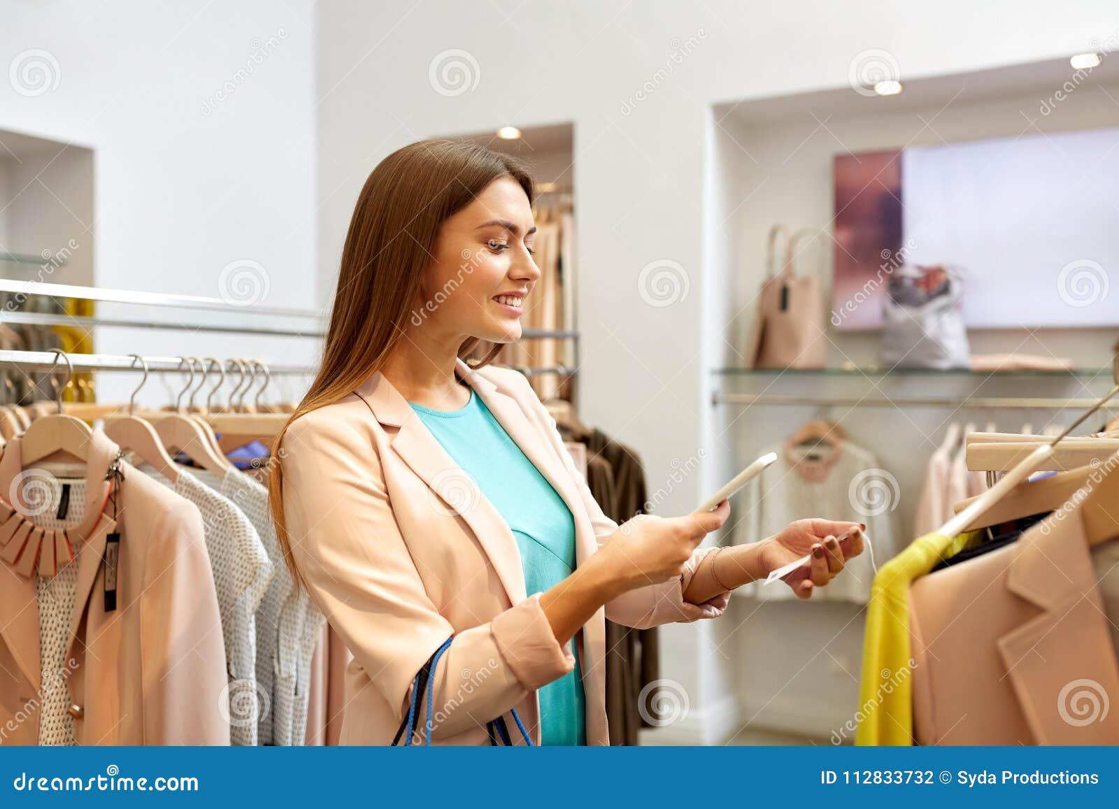 Szczęśliwa kobieta używa telefon app przy sklepem odzieżowym