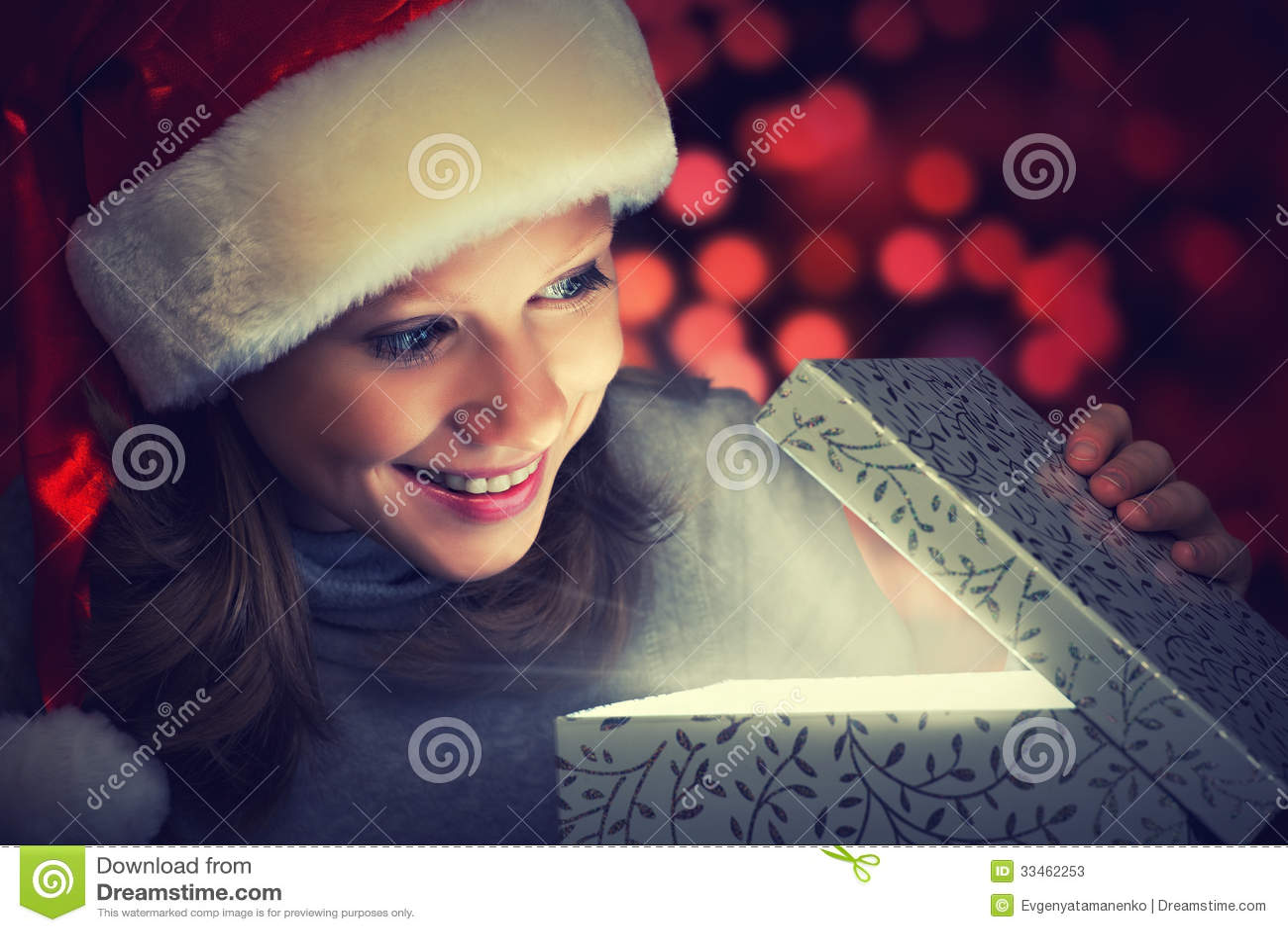 Szczęśliwa kobieta w Bożenarodzeniowej nakrętce otwiera magicznego pudełko