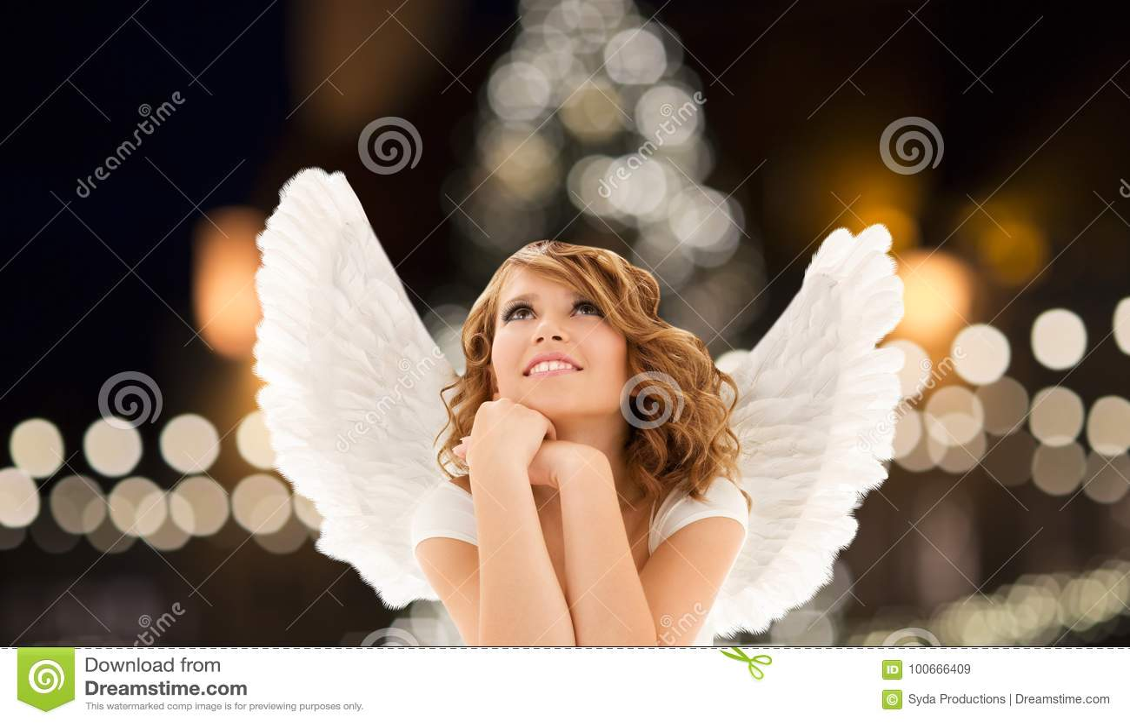 Szczęśliwa kobieta z aniołem uskrzydla nad bożonarodzeniowe światła