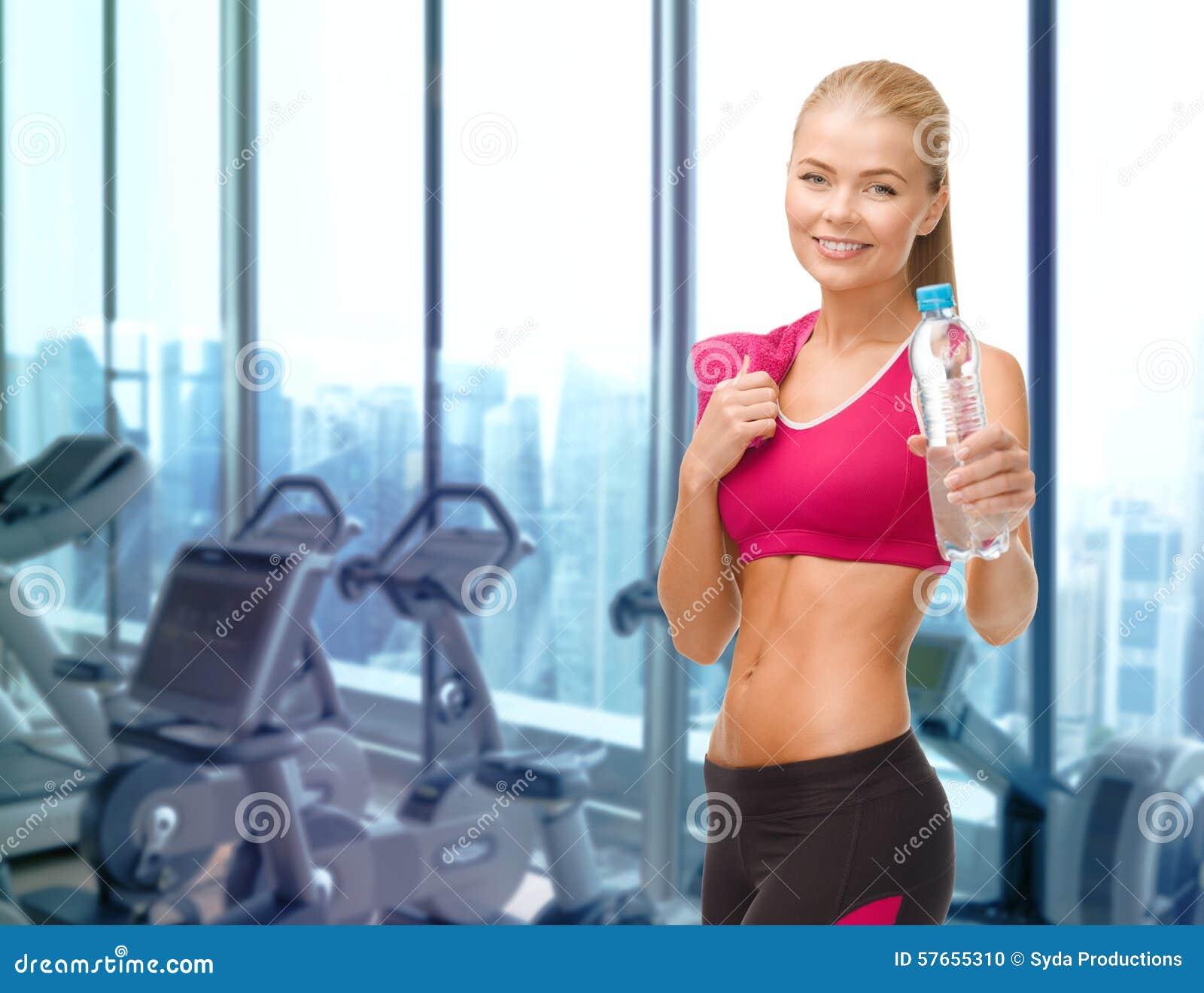 Szczęśliwa kobieta z butelką woda i ręcznik w gym