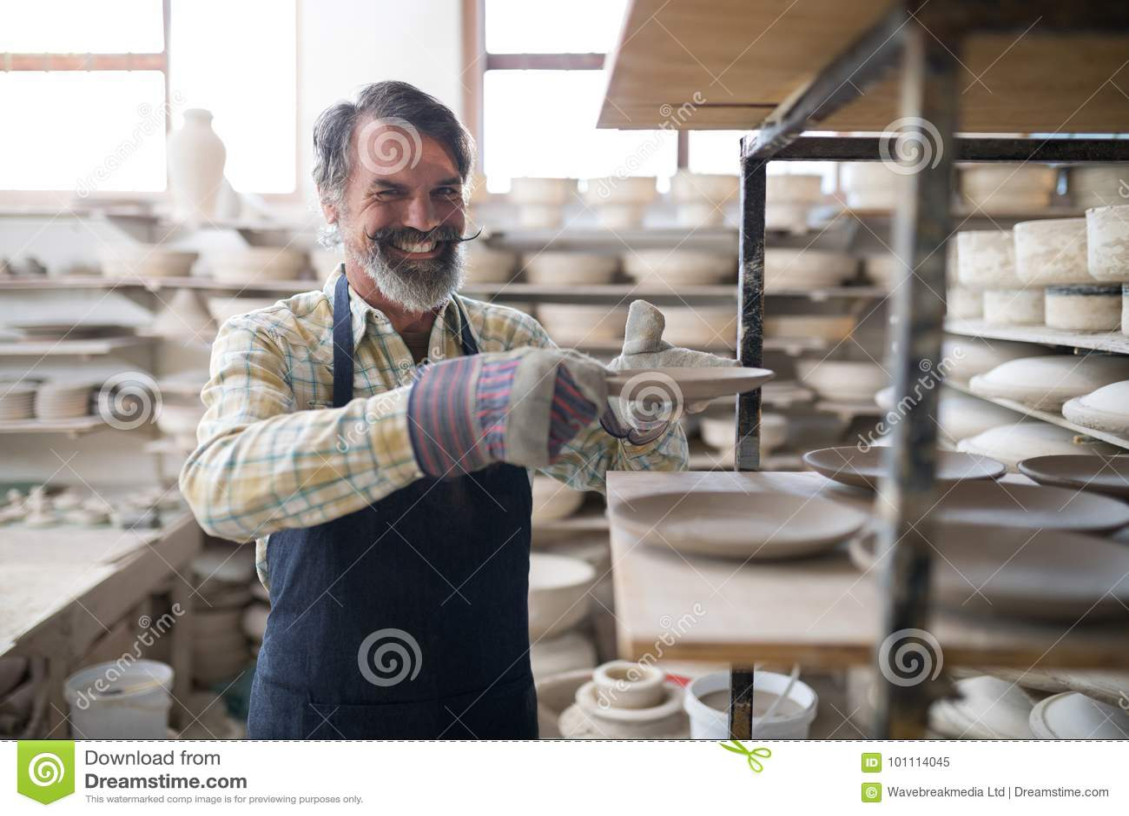 Szczęśliwa męska garncarka umieszcza półkową ob półkę