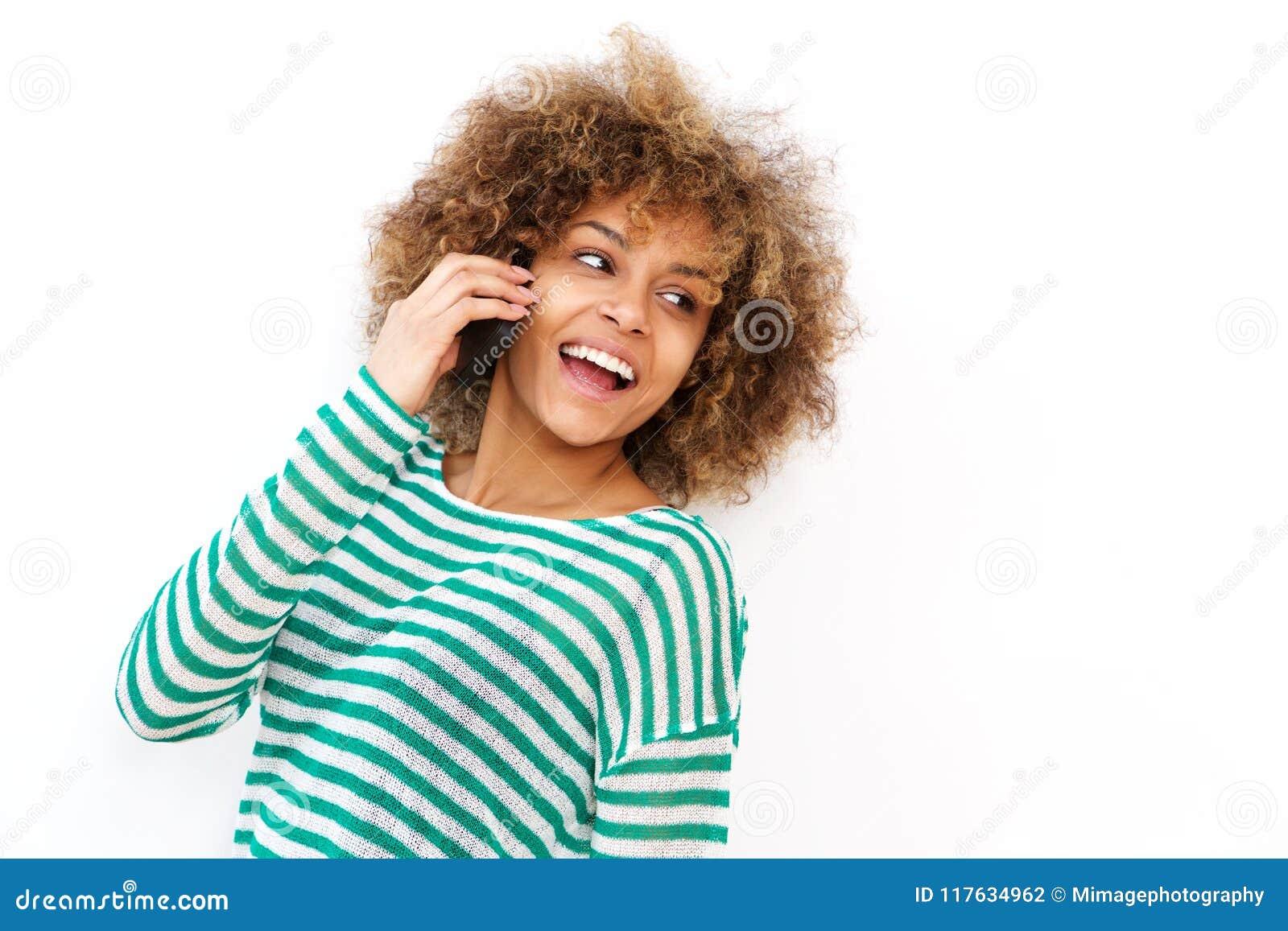 Szczęśliwa młoda amerykanin afrykańskiego pochodzenia kobieta opowiada na telefonie komórkowym białym tłem