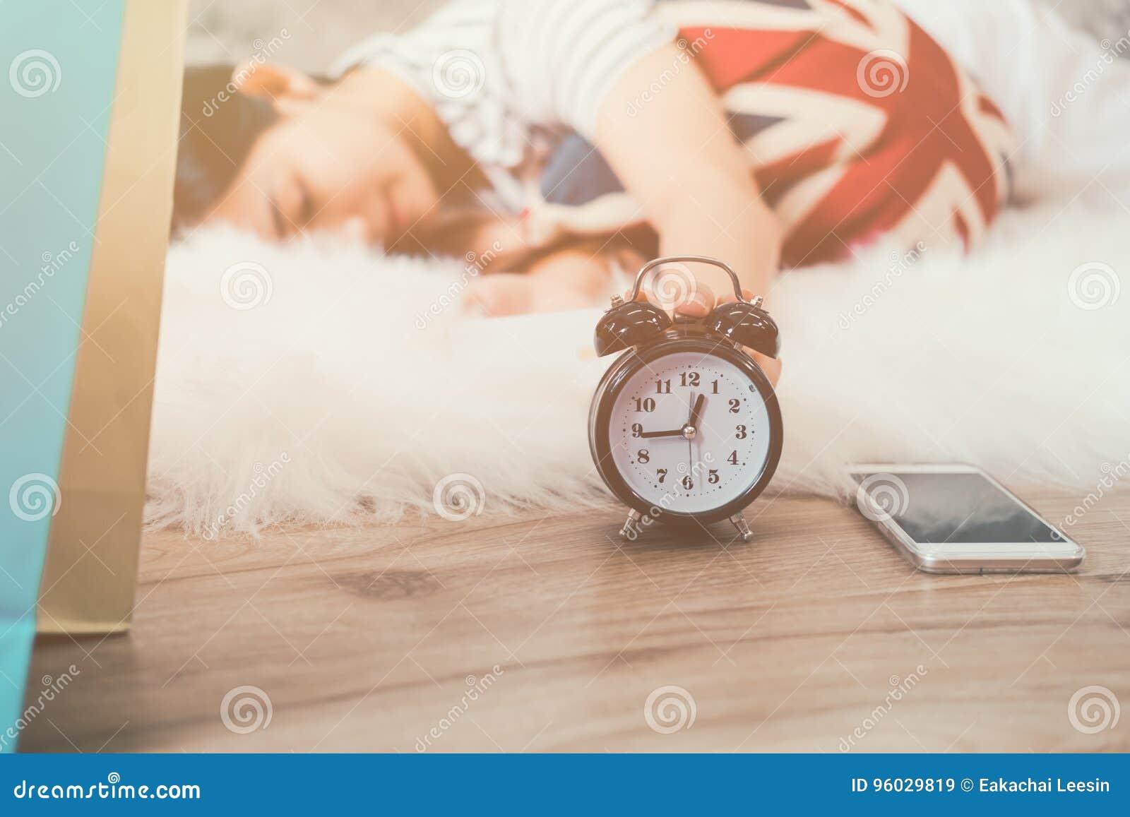 Szczęśliwa młoda azjatykcia kobieta budzi się up budzika i obraca daleko