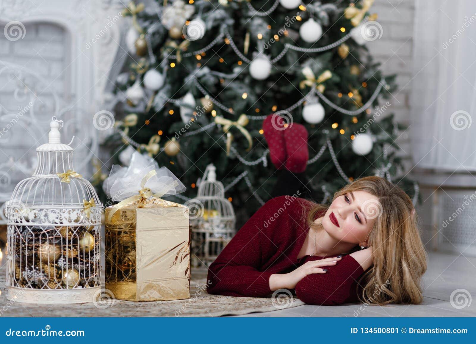 Szczęśliwa młoda dama z długie włosy prezentami grabą blisko choinki