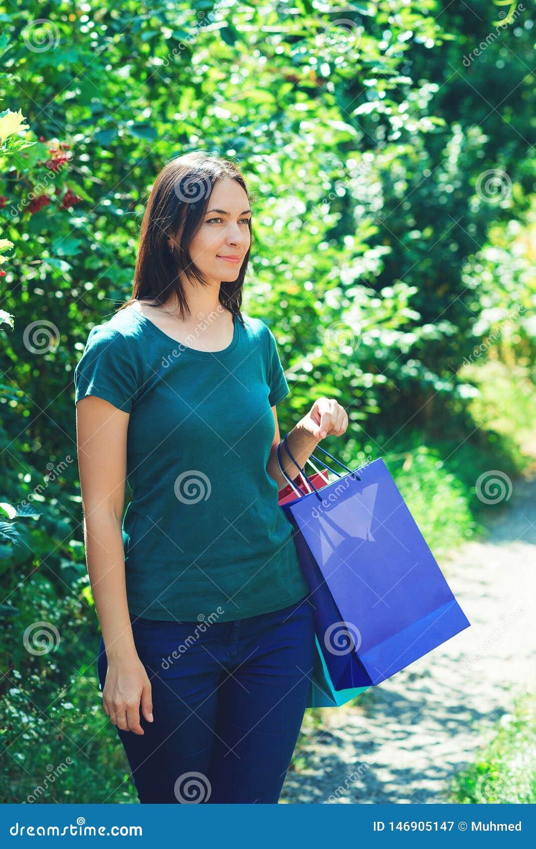 Szczęśliwa młoda kobieta cieszy się sezonowe sprzedaże z kolorowymi torbami na zakupy, patrzeje na boku wszystkie jaka? element?w