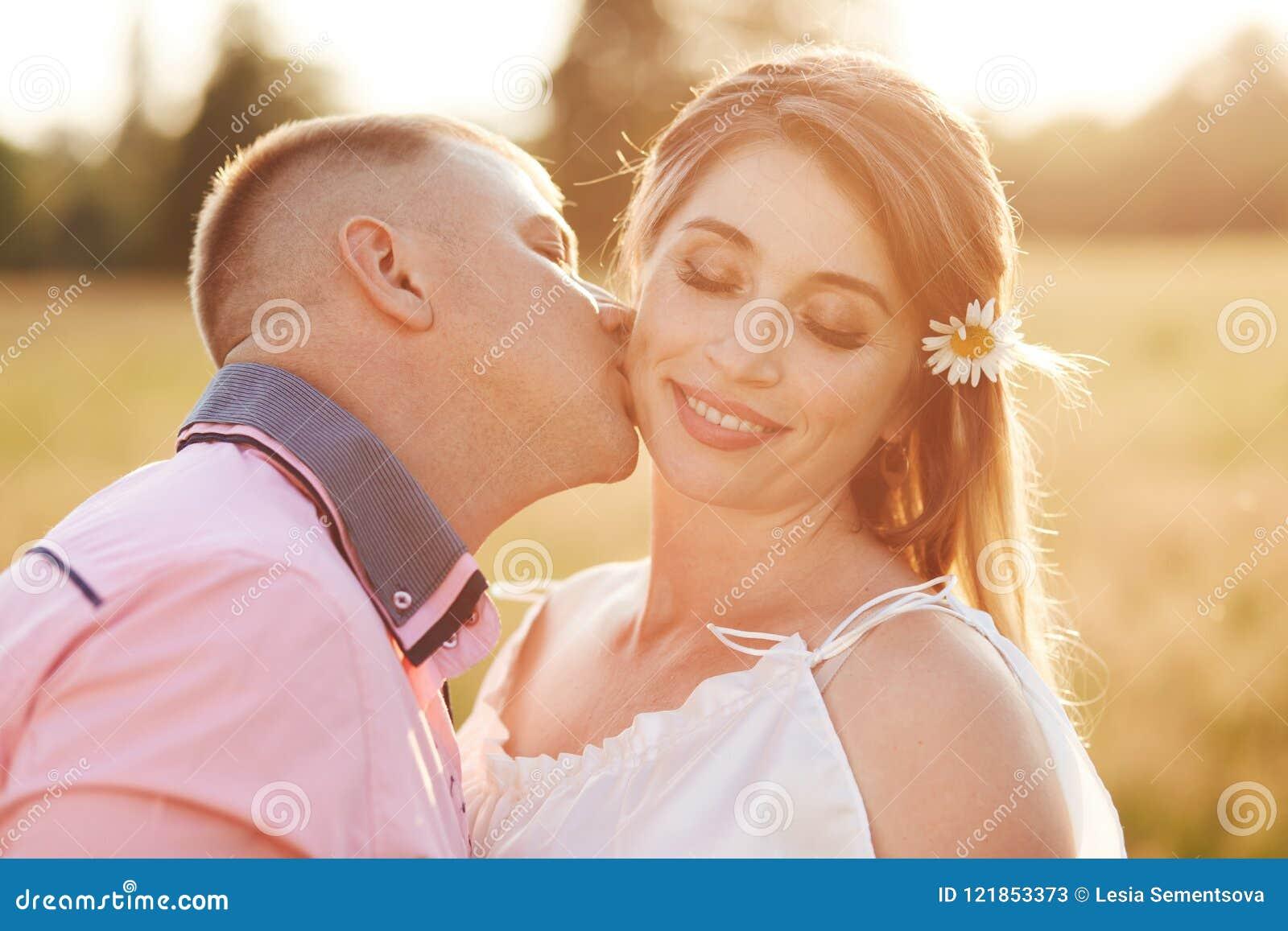 Szczęśliwa młoda kobieta otrzymywa buziaka od chłopaka, plenerowego spacer przez pole, pokazuje miłości each inny Uroczy pary poz