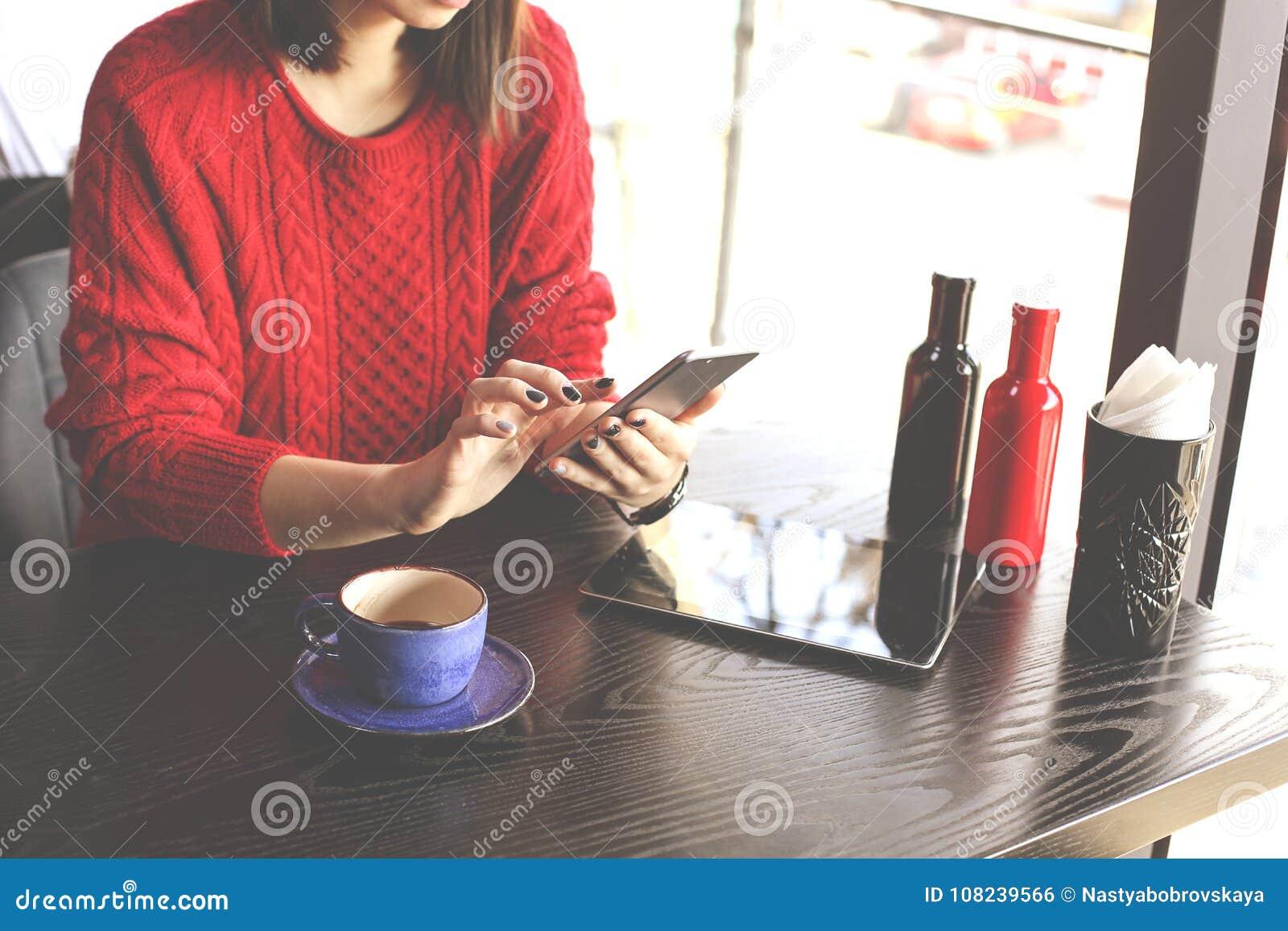 Szczęśliwa młoda kobieta pije cappuccino, używa pastylka komputer i opowiada na telefonie w, latte, macchiato, herbata, sklep z k