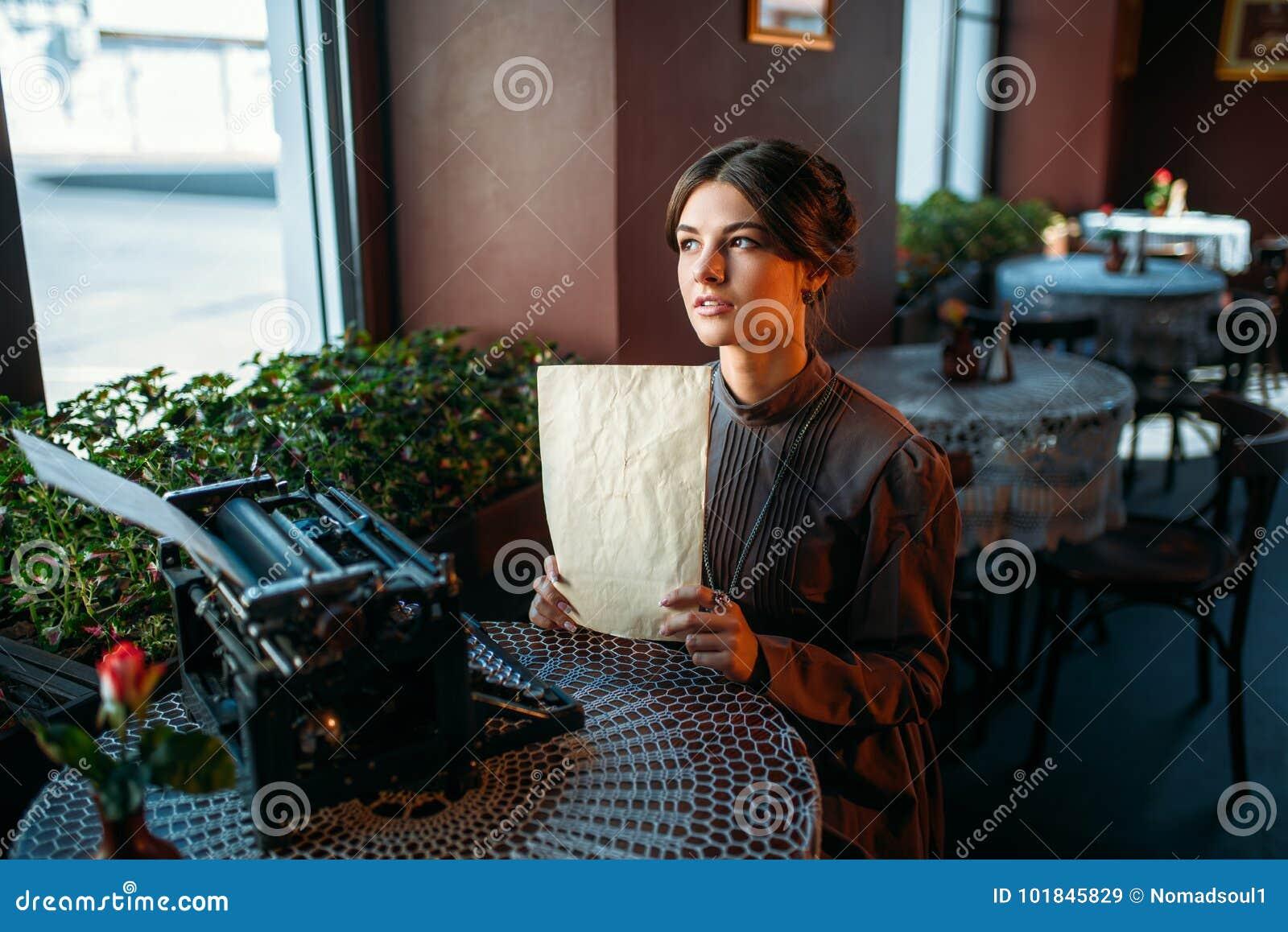 Szczęśliwa młoda kobieta siedzi stołem w kawiarni
