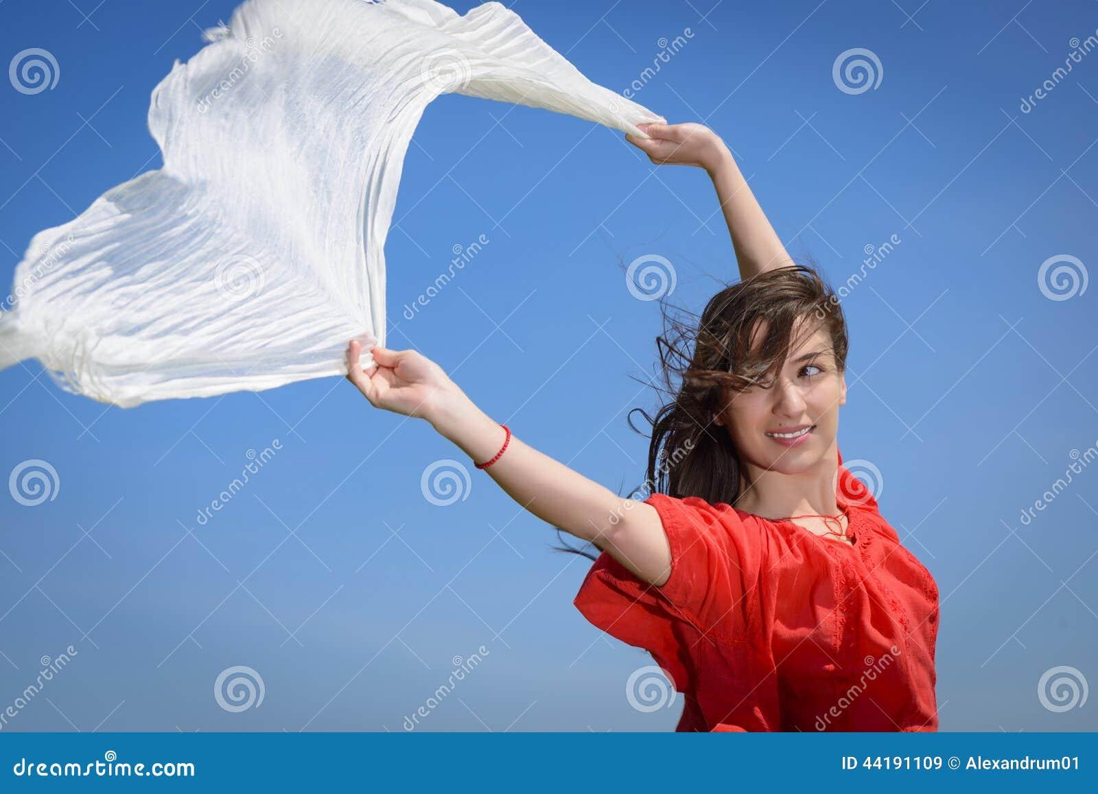 Szczęśliwa młoda kobieta trzyma białego szalika z rozpieczętowanymi rękami wyraża wolność, plenerowy strzał przeciw niebieskiemu