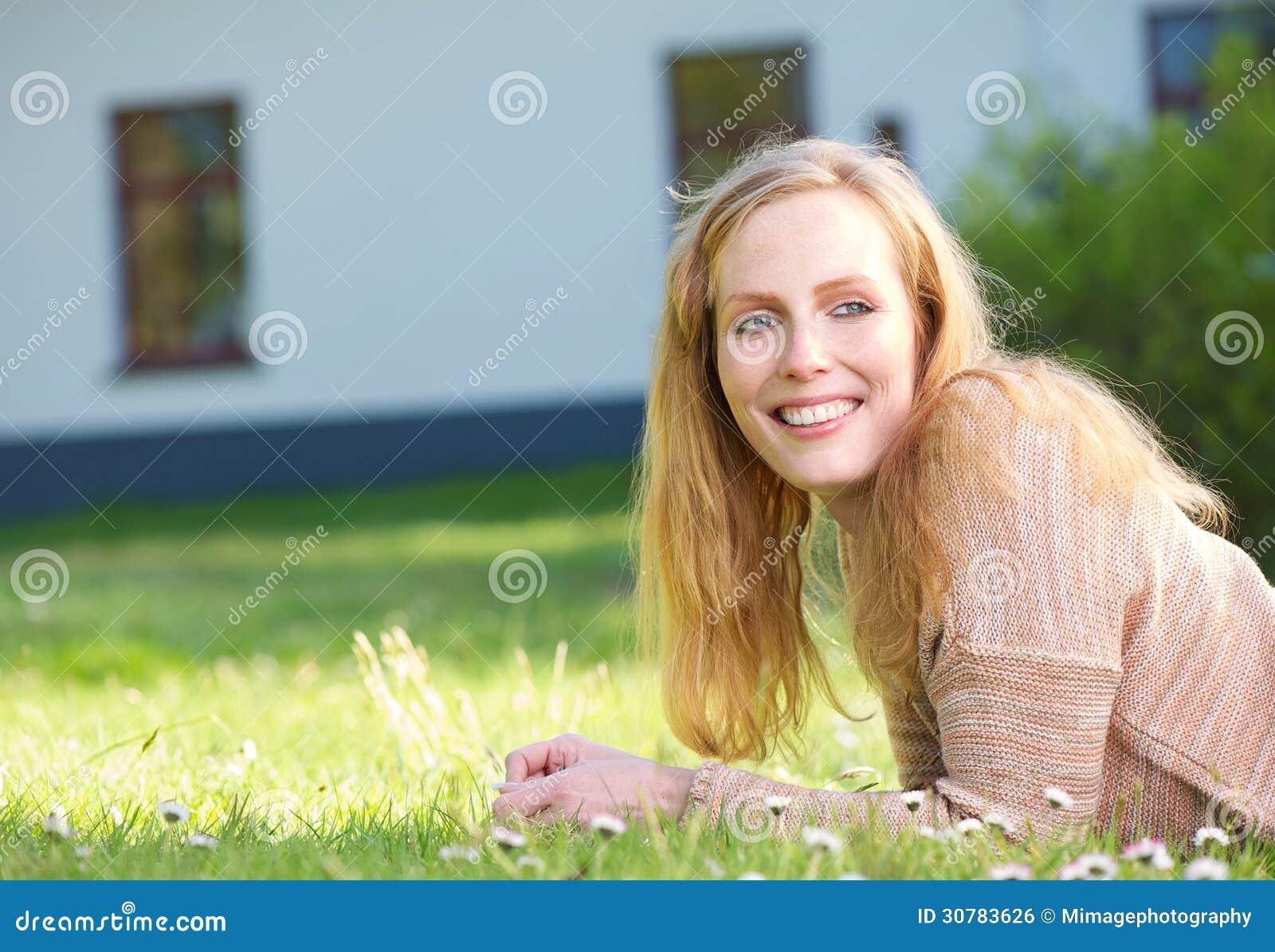 Szczęśliwa młoda kobieta uśmiechnięta i relaksuje na trawie outdoors