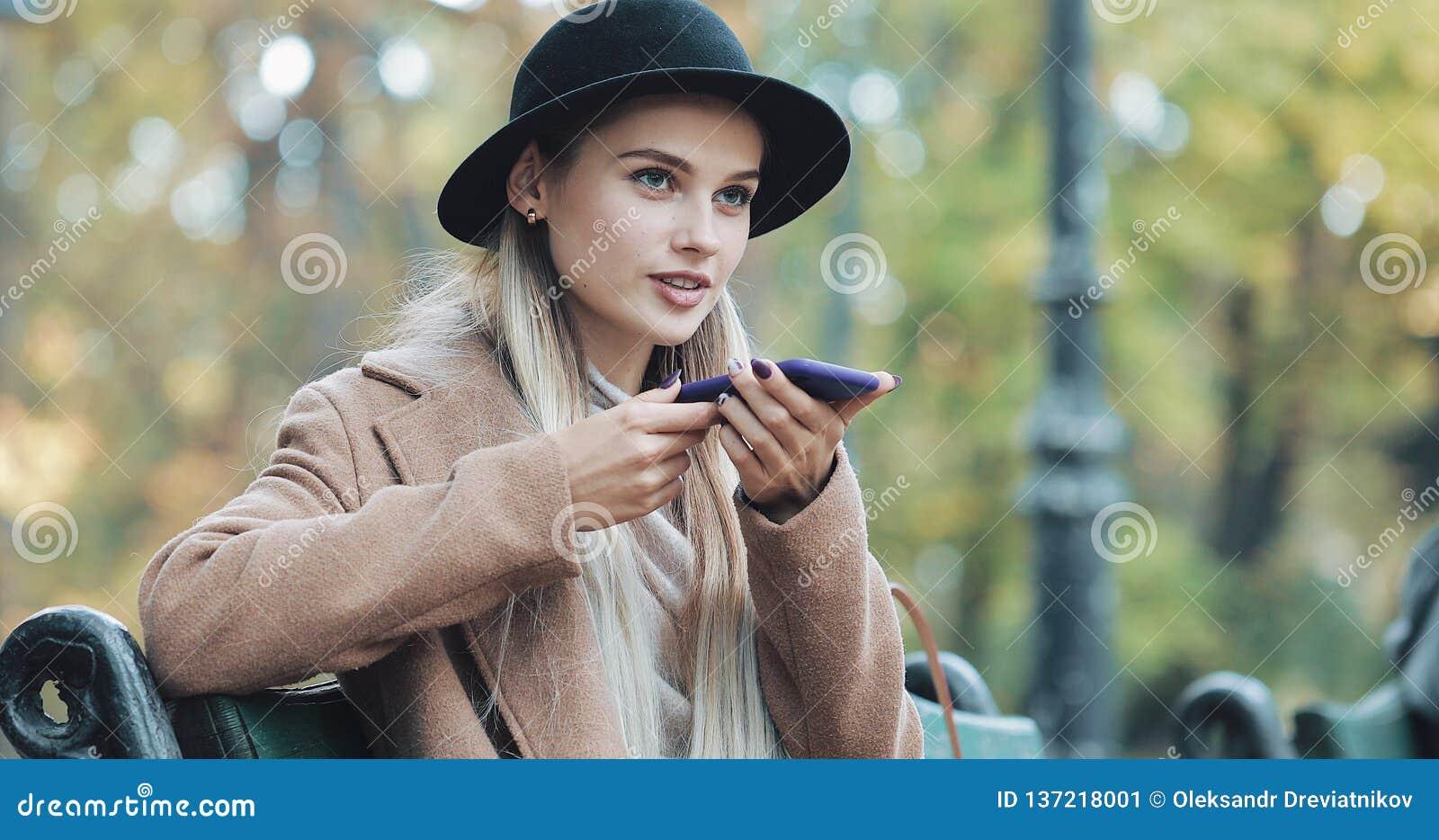 Szczęśliwa młoda kobieta używa smartphone głosu rozpoznania funkcję Ona Siedzi na ławce w jesień dyktatach i parku