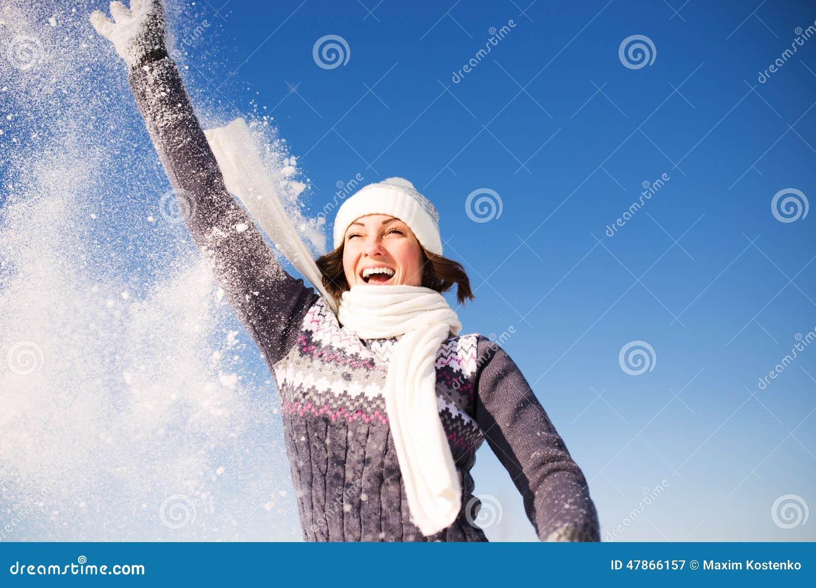 Szczęśliwa młoda kobieta zabawę i cieszy się świeżego śnieg