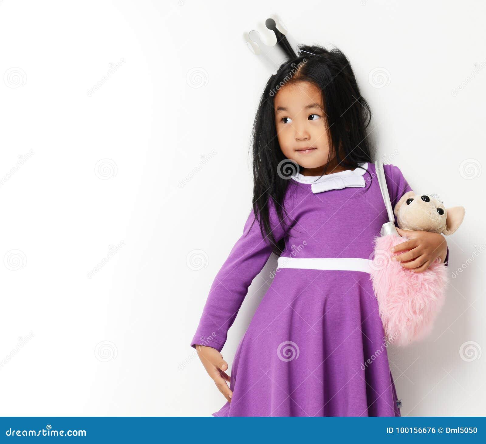 Szczęśliwa młoda mała azjatykcia dziecko dziewczyna przygotowywająca dla urodziny z małym psem w torbie patrzeje kąt