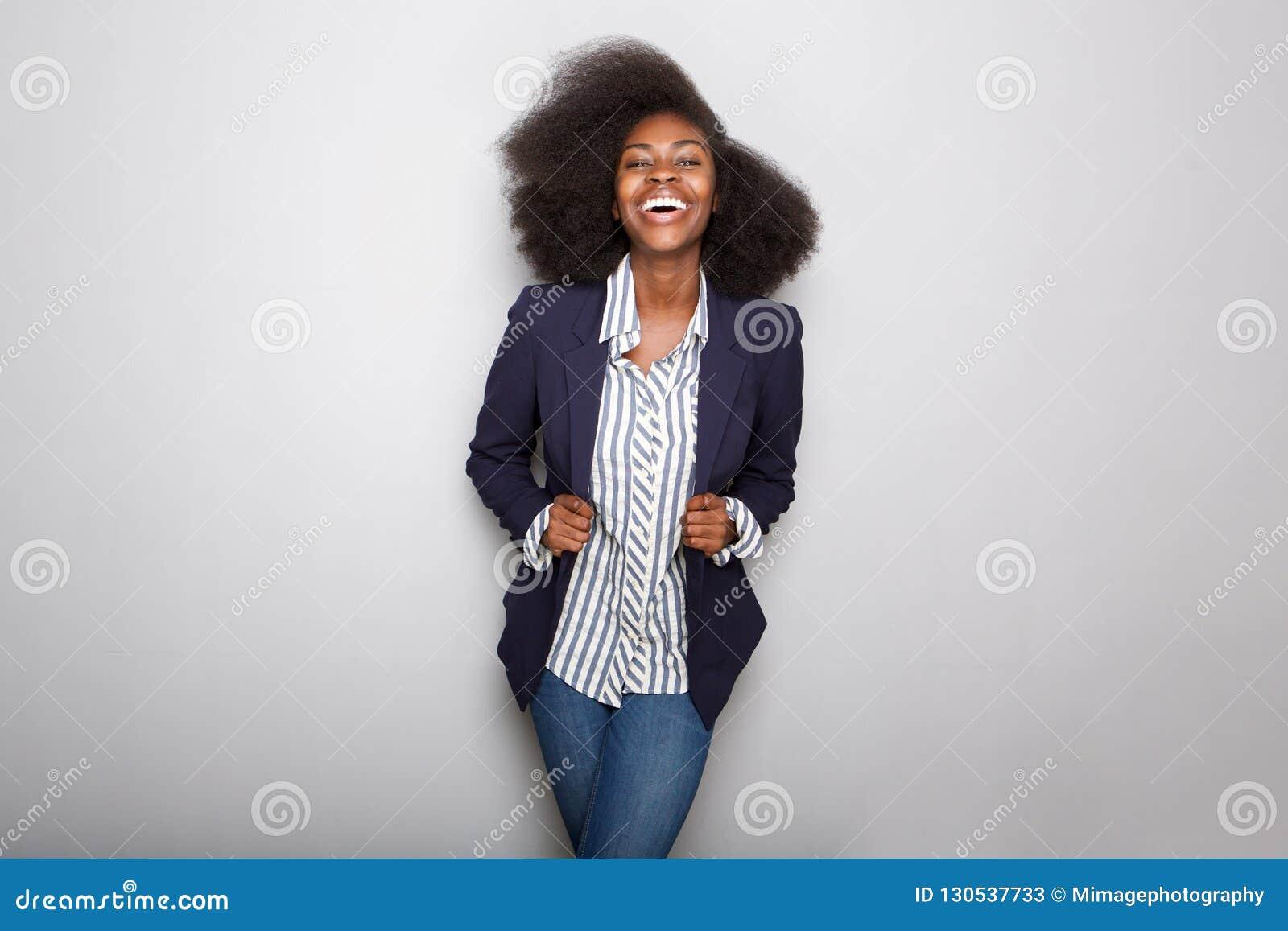 Szczęśliwa młoda murzynka z blezerem przeciw szaremu tłu