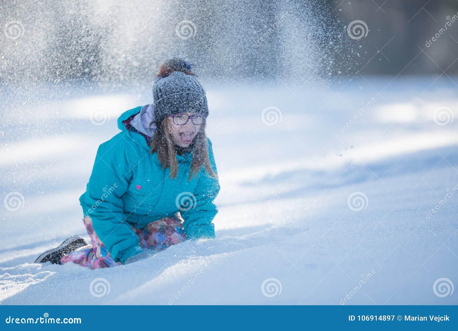 Szczęśliwa młoda nastoletnia dziewczyna w ciepłej odzieży bawić się z śniegiem