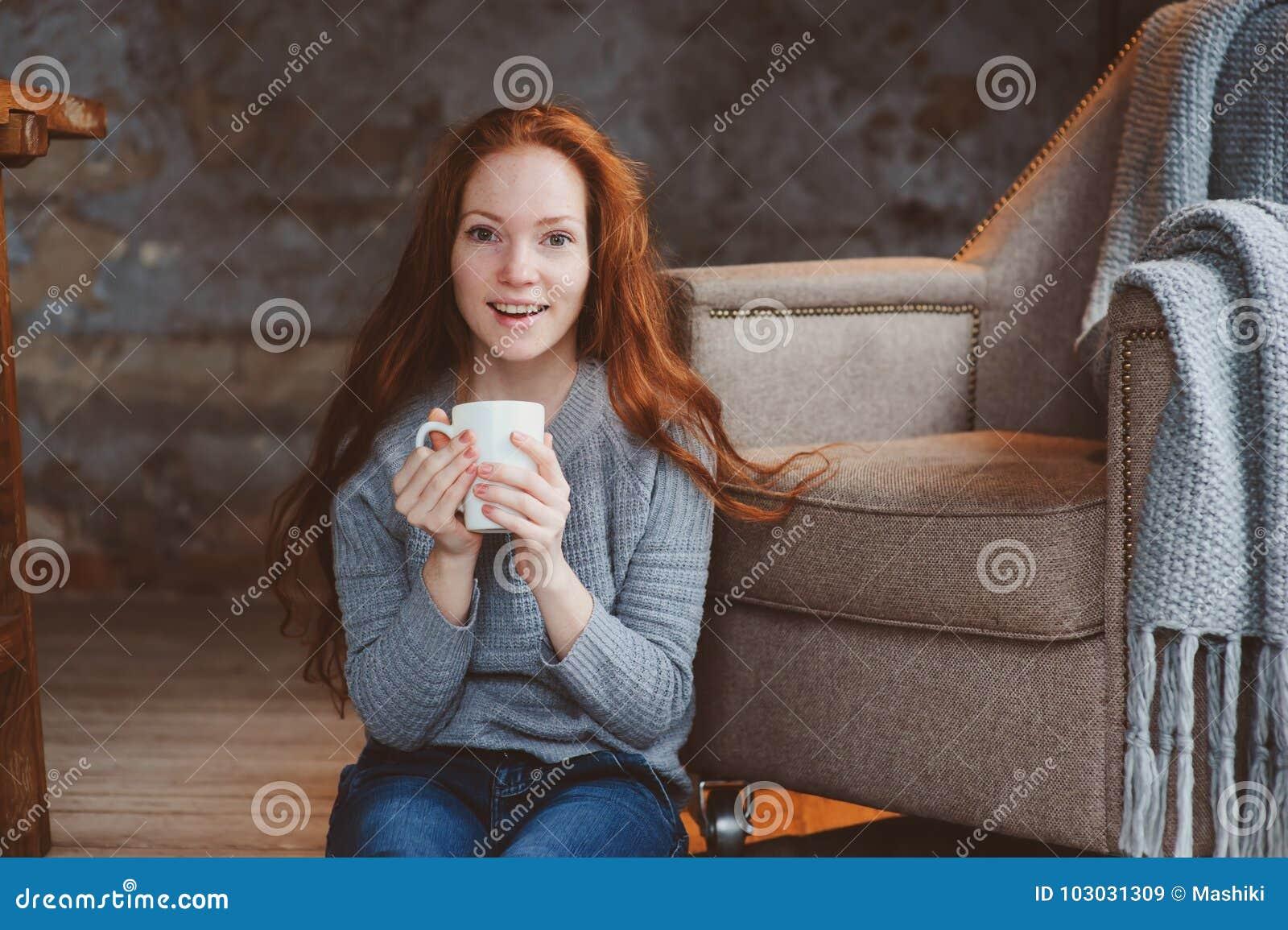 Szczęśliwa młoda readhead kobieta pije gorącą kawę lub herbaty w domu Spokojny i wygodny weekend w zimie