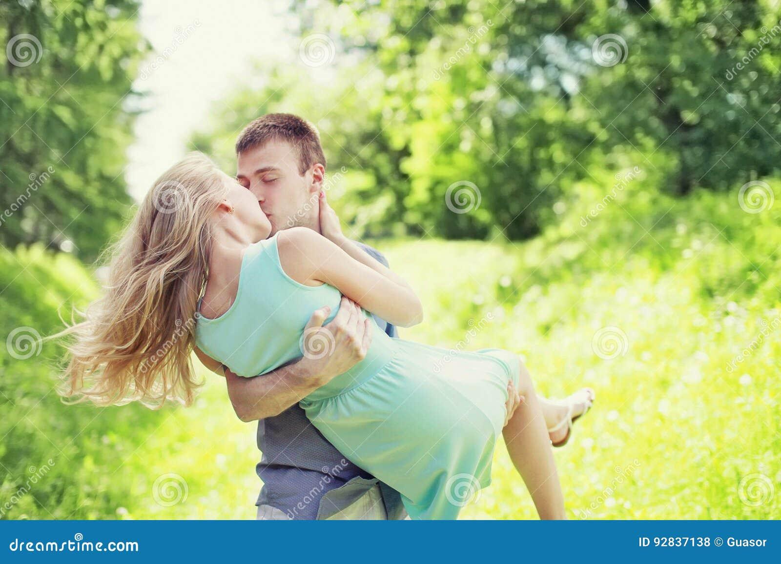Szczęśliwa młoda słodka para całuje, mężczyzna i kobieta w miłości, trzyma ona na przy trawą ręki