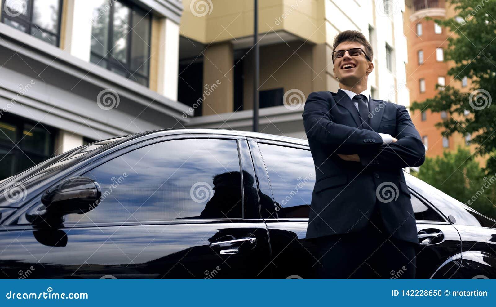 Szczęśliwa młoda samiec stoi bezczynnie nowego luksusowego samochód, urzędnik dostaje promocję