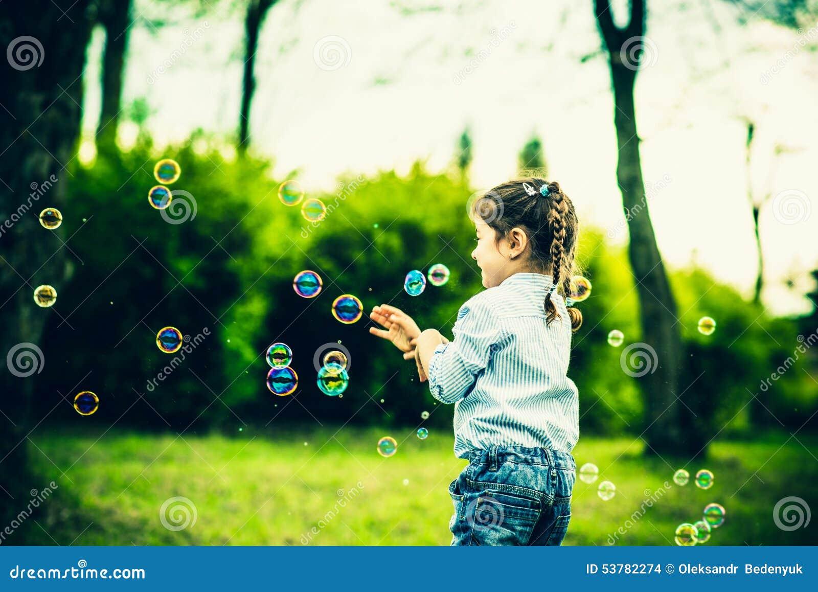 Szczęśliwa mała ładna dziewczyna plenerowa w parku