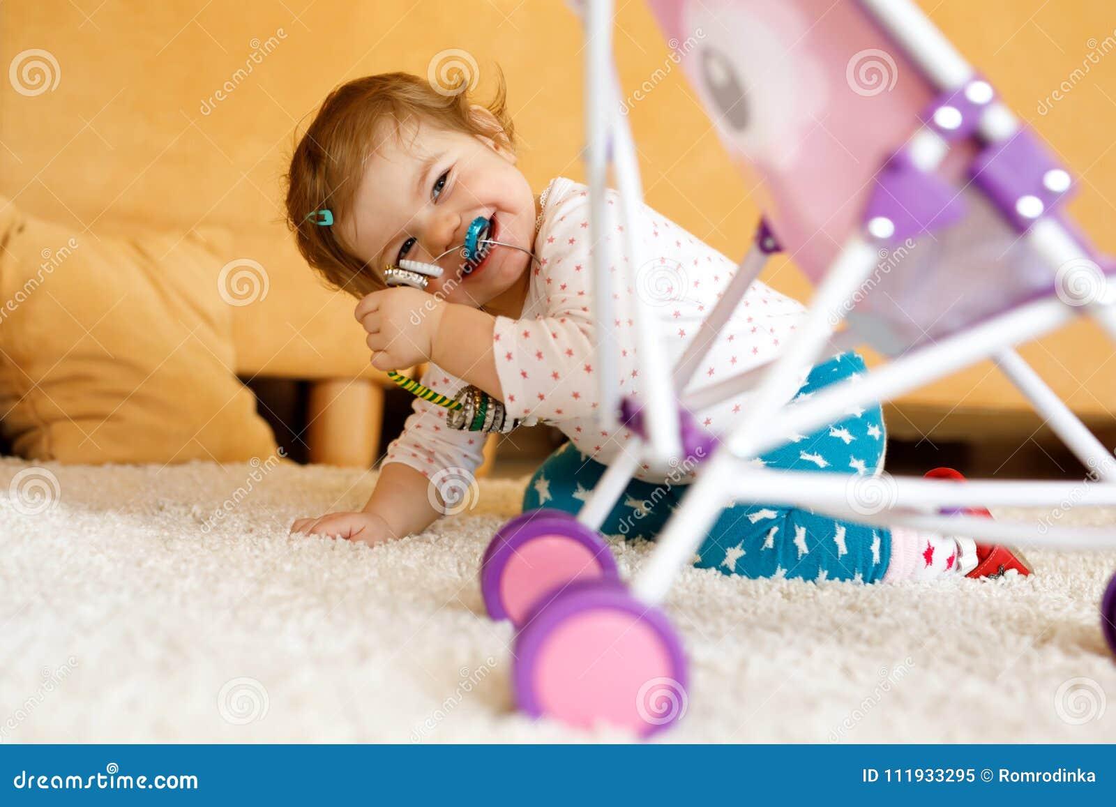 Szczęśliwa mała berbeć dziewczynka bawić się kryjówkę aport w domu - i - Dziecko ma zabawę z rodzicami lub rodzeństwami